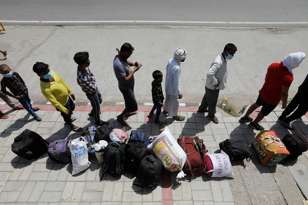 Migrant workers and their families wait to get on a bus to reach a railway station to board a train to their home state of Uttar Pradesh, during an extended lockdown to slow the spreading of the coronavirus disease (COVID-19), in New Delhi, India, May 26, 2020. REUTERS/Adnan Abidi - RC27WG95CCQT
