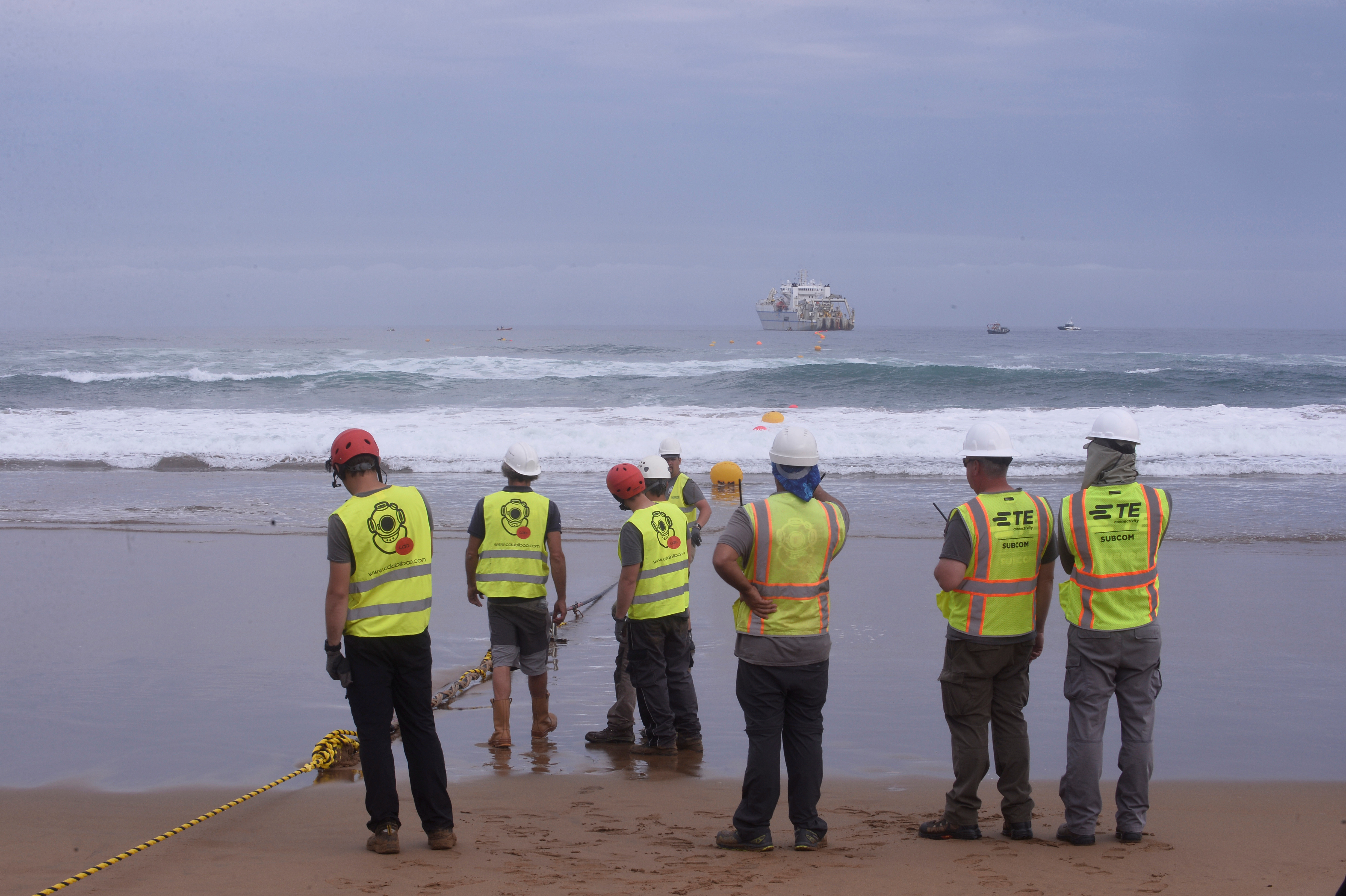 Workers observe a fiber optic cable from a cable laying ship at Arrietara beach, near Bilbao, northern Spain, June 13, 2017, as Facebook Inc. and Microsoft Corp. join forces to build an underwater fiber optic cable across the Atlantic Ocean, linking Europe and the USA. REUTERS/Vincent West - RC1F713B4F60