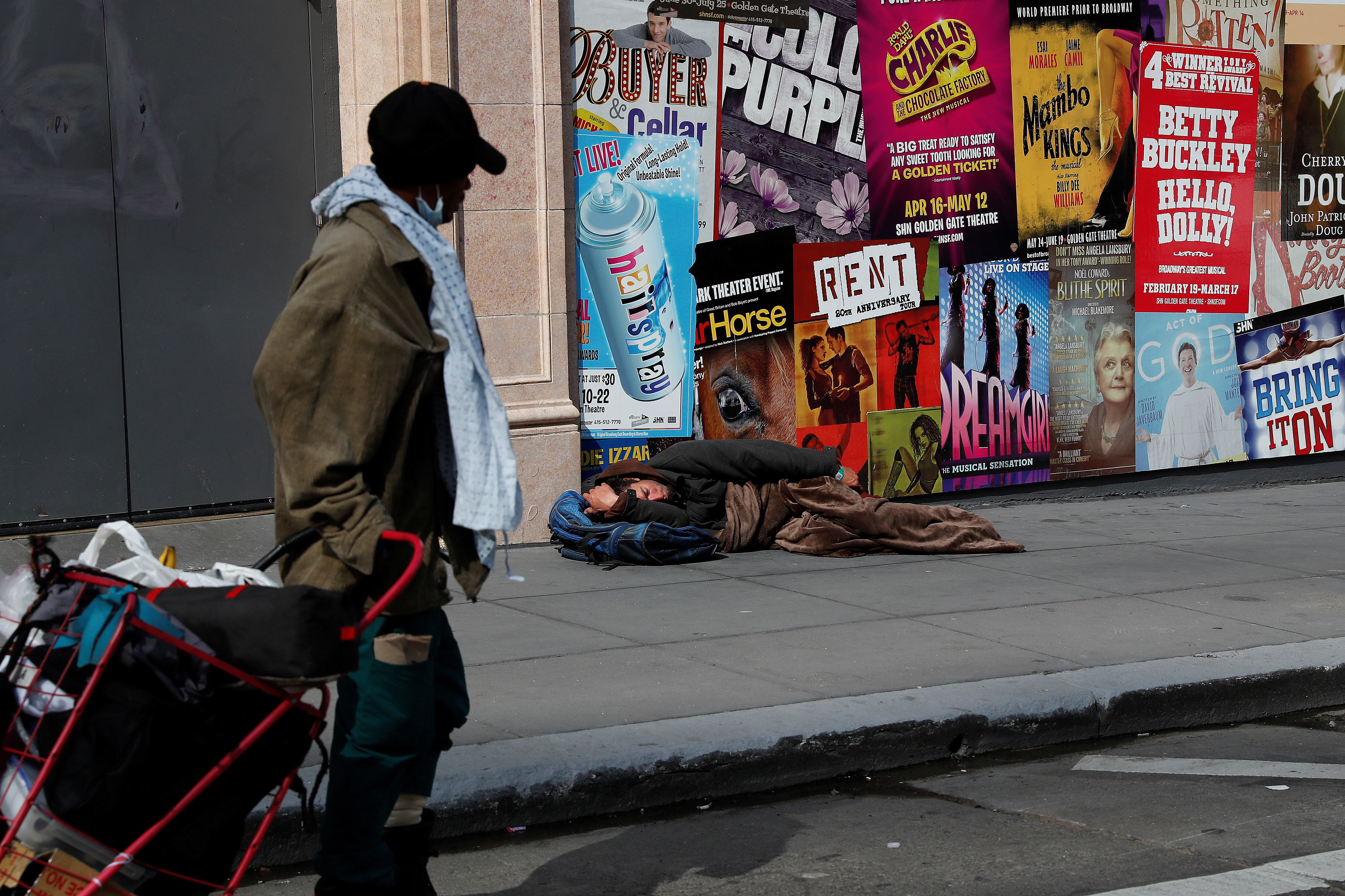 A man sleeps on the sidewalk amid an outbreak of the coronavirus disease (COVID-19), in San Francisco, California, U.S. March 27, 2020. Picture taken March 27, 2020.