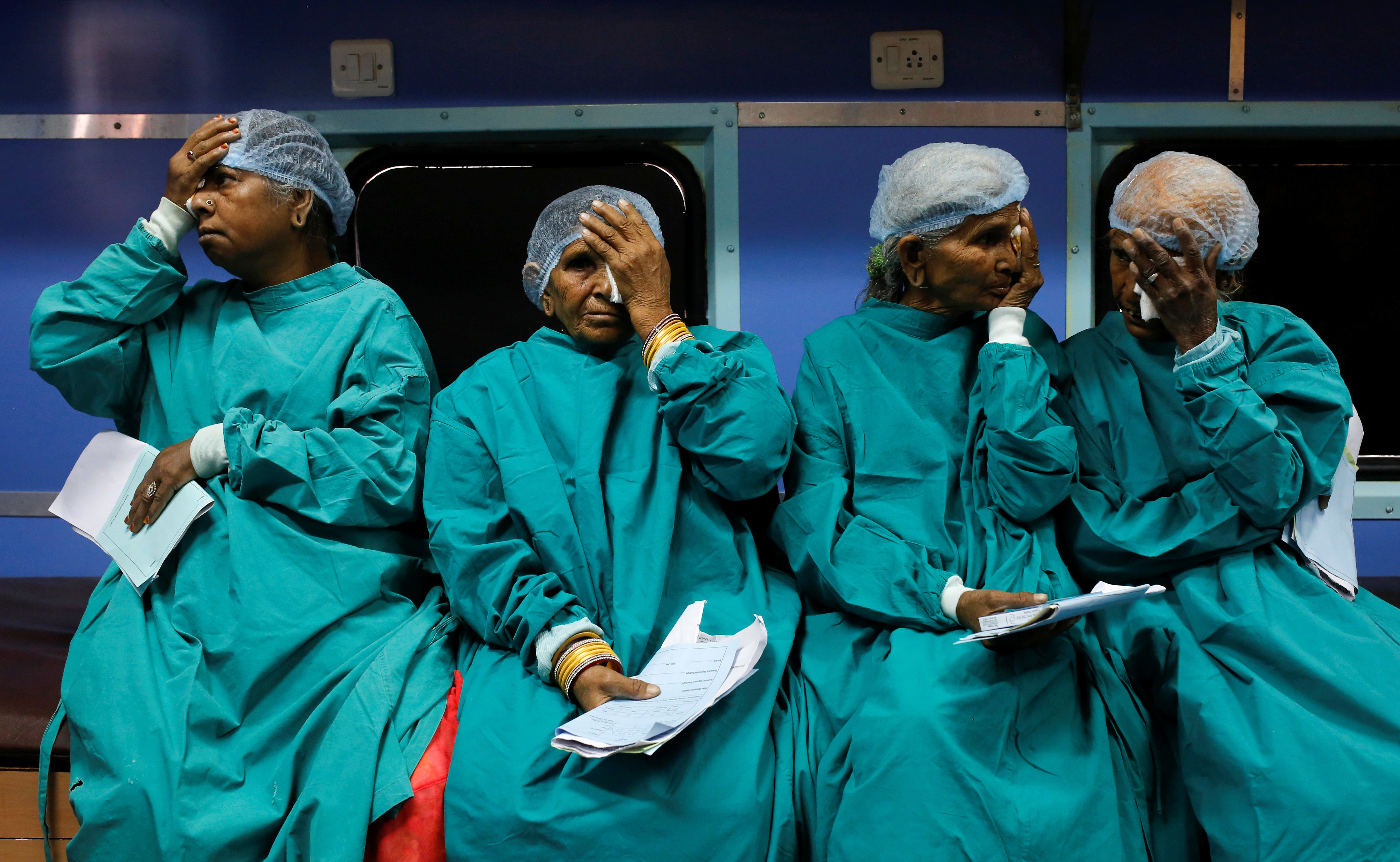 """Patients cover their eyes as they wait before their cataract surgery on the Lifeline Express, a hospital built inside a seven-coach train, at a railway station in Jalore, India, March 31, 2018. REUTERS/Danish Siddiqui      SEARCH """"LIFELINE"""" FOR THIS STORY. SEARCH """"WIDER IMAGE"""" FOR ALL STORIES. TPX IMAGES OF THE DAY - RC13F252F8E0"""