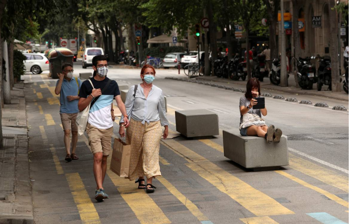 People walk by a pedestrian zone painted in blue and yellow at a junction in Barcelona, Spain, July 26, 2021.