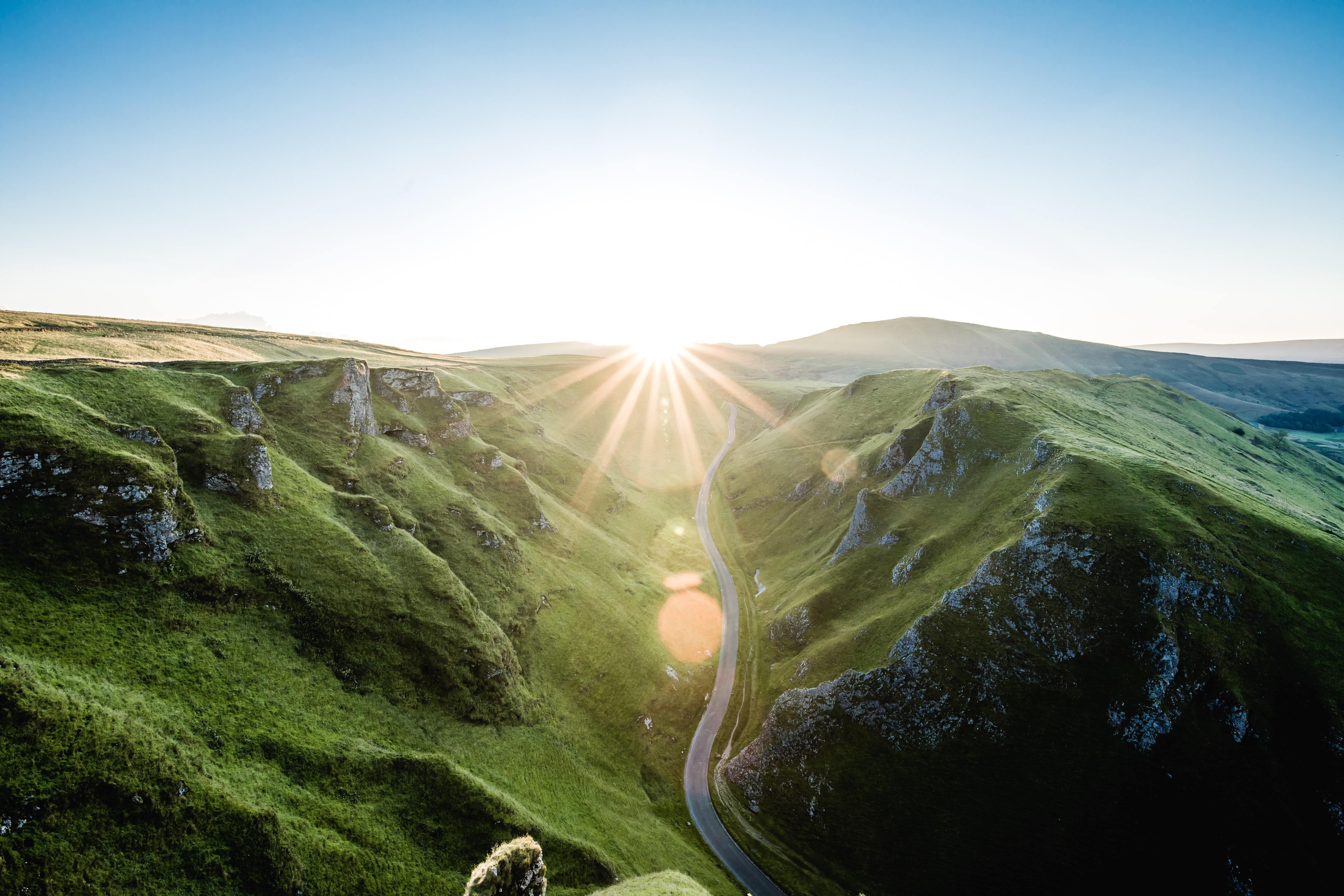 Sun rising over a lush green valley