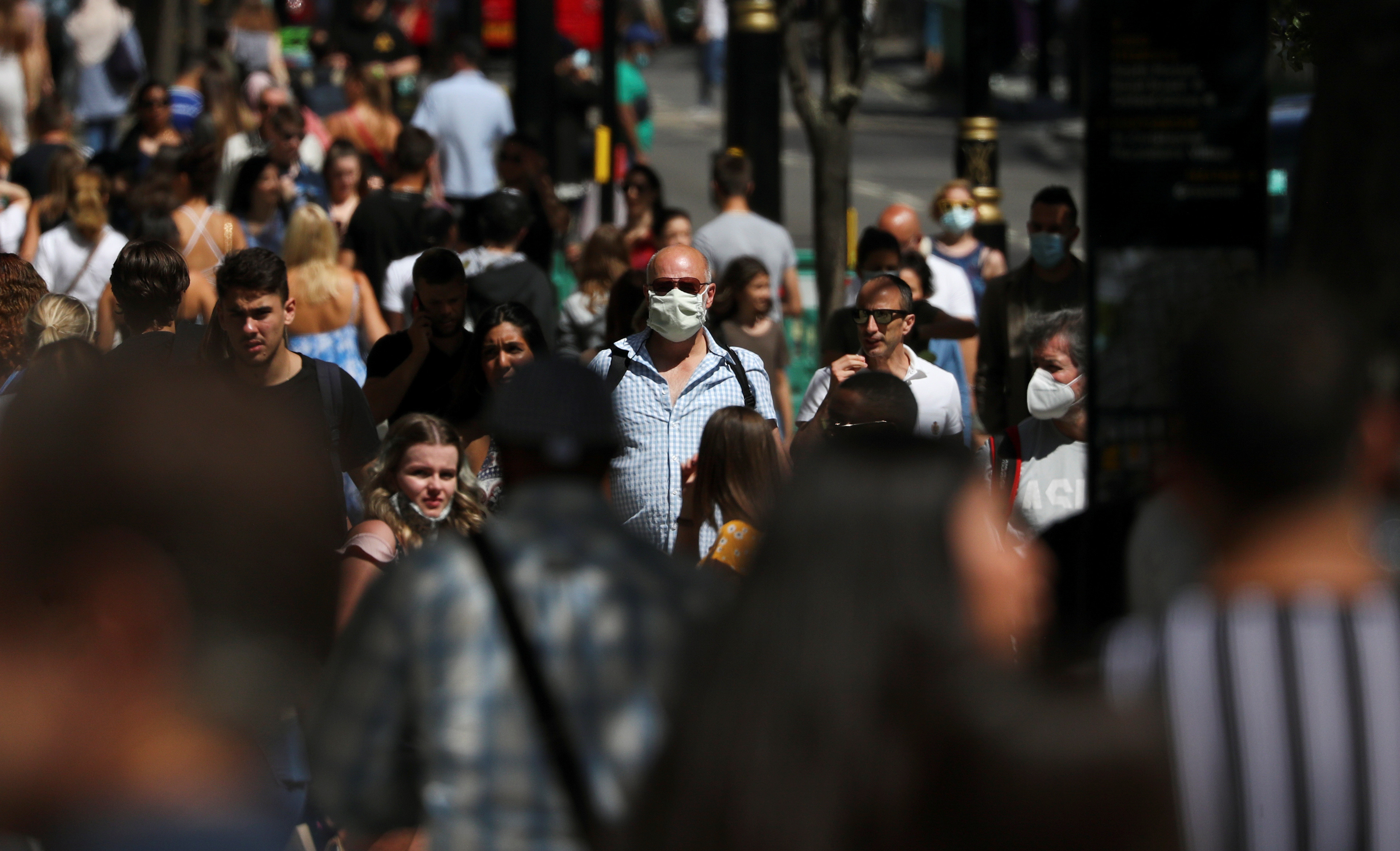 A man wearing a face mask is pictured among a crowd in Oxford Street, following the coronavirus disease (COVID-19) outbreak, in London, Britain, July 18, 2020. REUTERS/Simon Dawson - RC2QVH9PV8MP