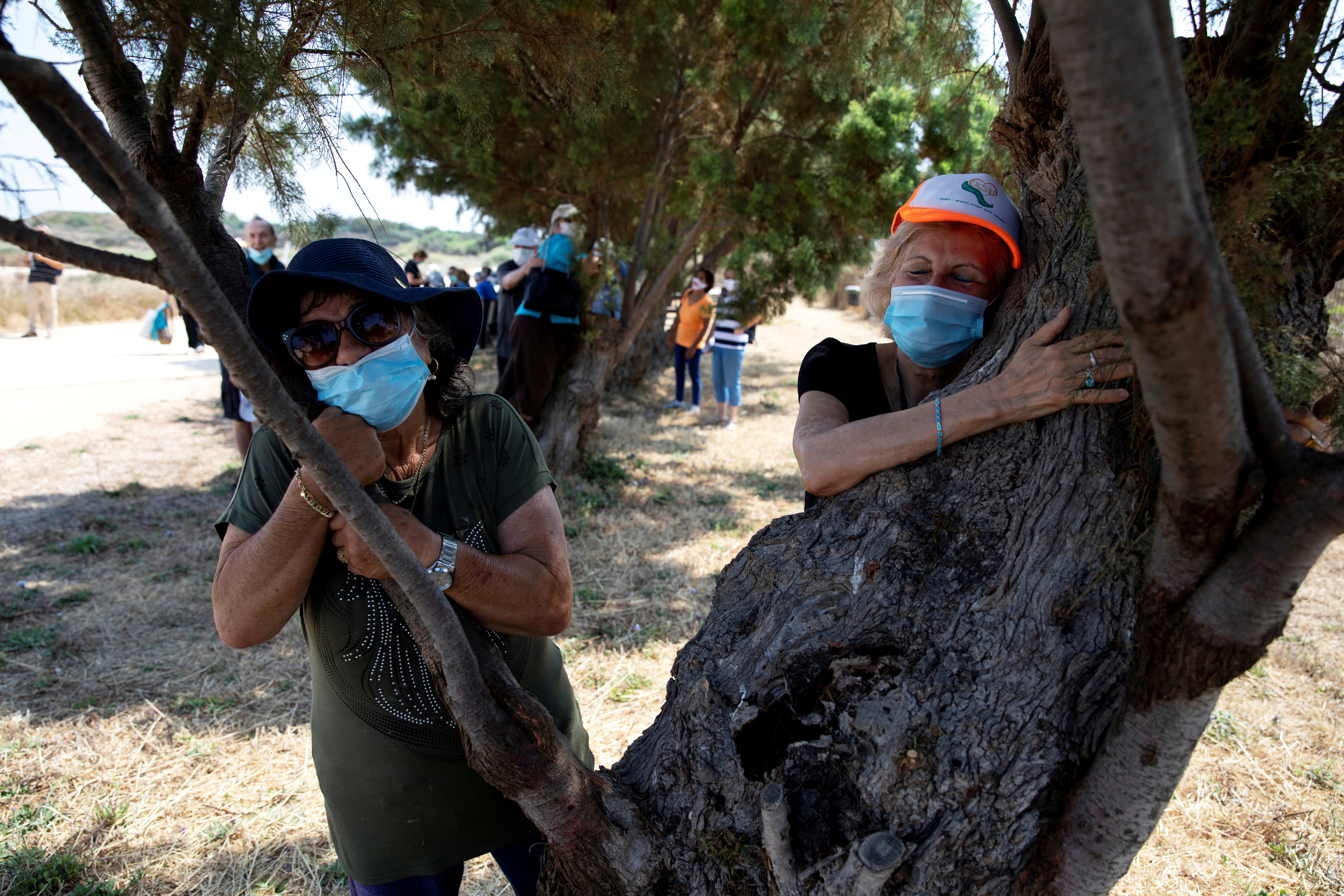 People take part in a campaign by Israel's Nature and Parks Authority calling on Israelis to join sightseeing tours and find comfort in tree hugging amid a spike in the coronavirus disease (COVID-19), in Apollonia National Park, near Herzliya, Israel July 7, 2020. Picture taken July 7, 2020. REUTERS/Ronen Zvulun     TPX IMAGES OF THE DAY - RC2ASH9LBMND