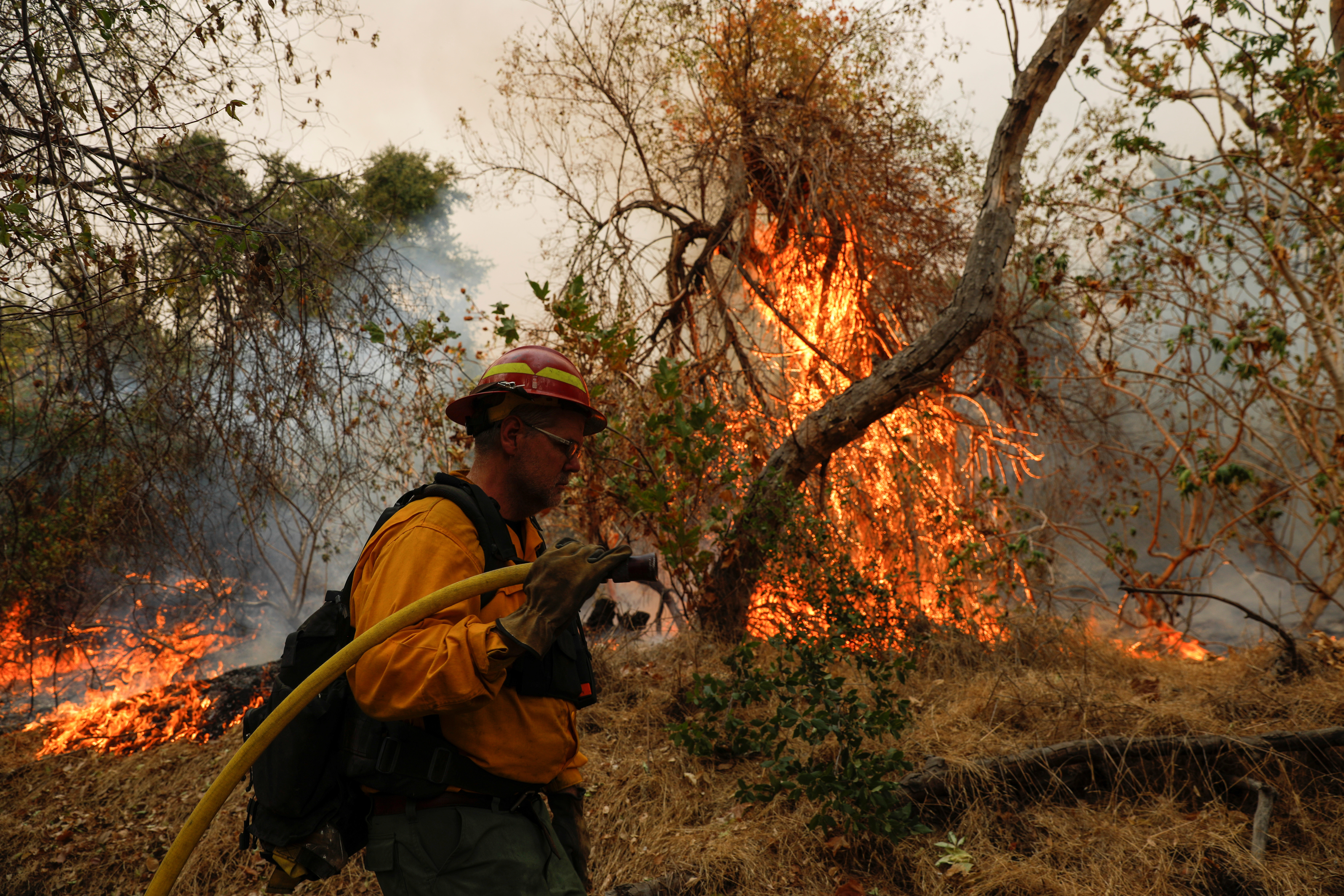 A firefighter works to extinguish the Bobcat Fire after an evacuation was ordered for the residents of Arcadia, California, U.S., September 13, 2020. REUTERS/Patrick T. Fallon - RC20YI9T4GX5