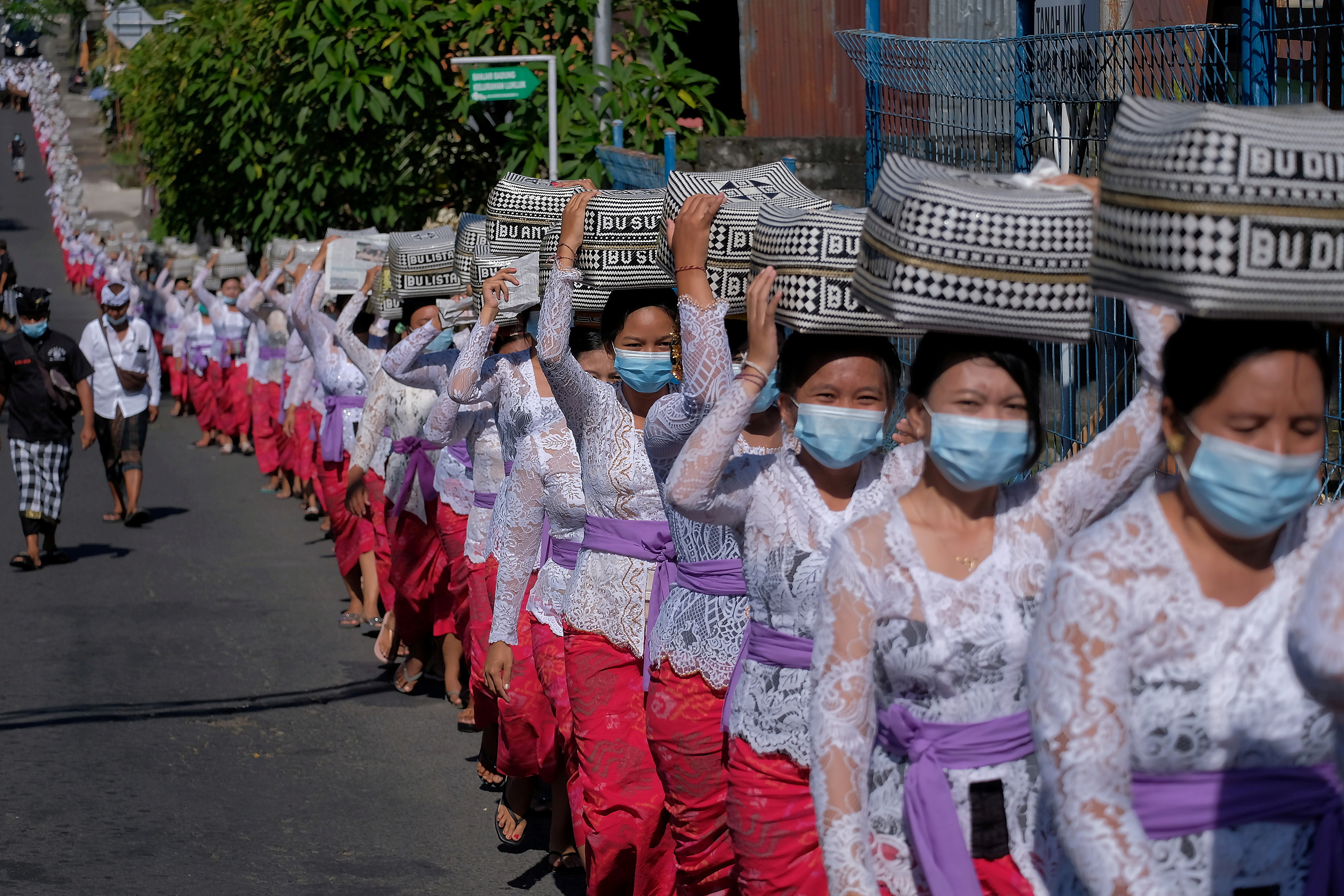 Balinese Hindus wearing protective masks carry offerings as they celebrate the Galungan religious holiday at Lukluk village, amid the coronavirus disease (COVID-19) pandemic, in Badung, Bali, Indonesia April 14, 2021. Nyoman Hendra Wibowo/Antara Foto via REUTERS ATTENTION EDITORS - THIS IMAGE WAS PROVIDED BY THIRD PARTY. MANDATORY CREDIT. INDONESIA OUT.     TPX IMAGES OF THE DAY - RC2PVM9K2L4J