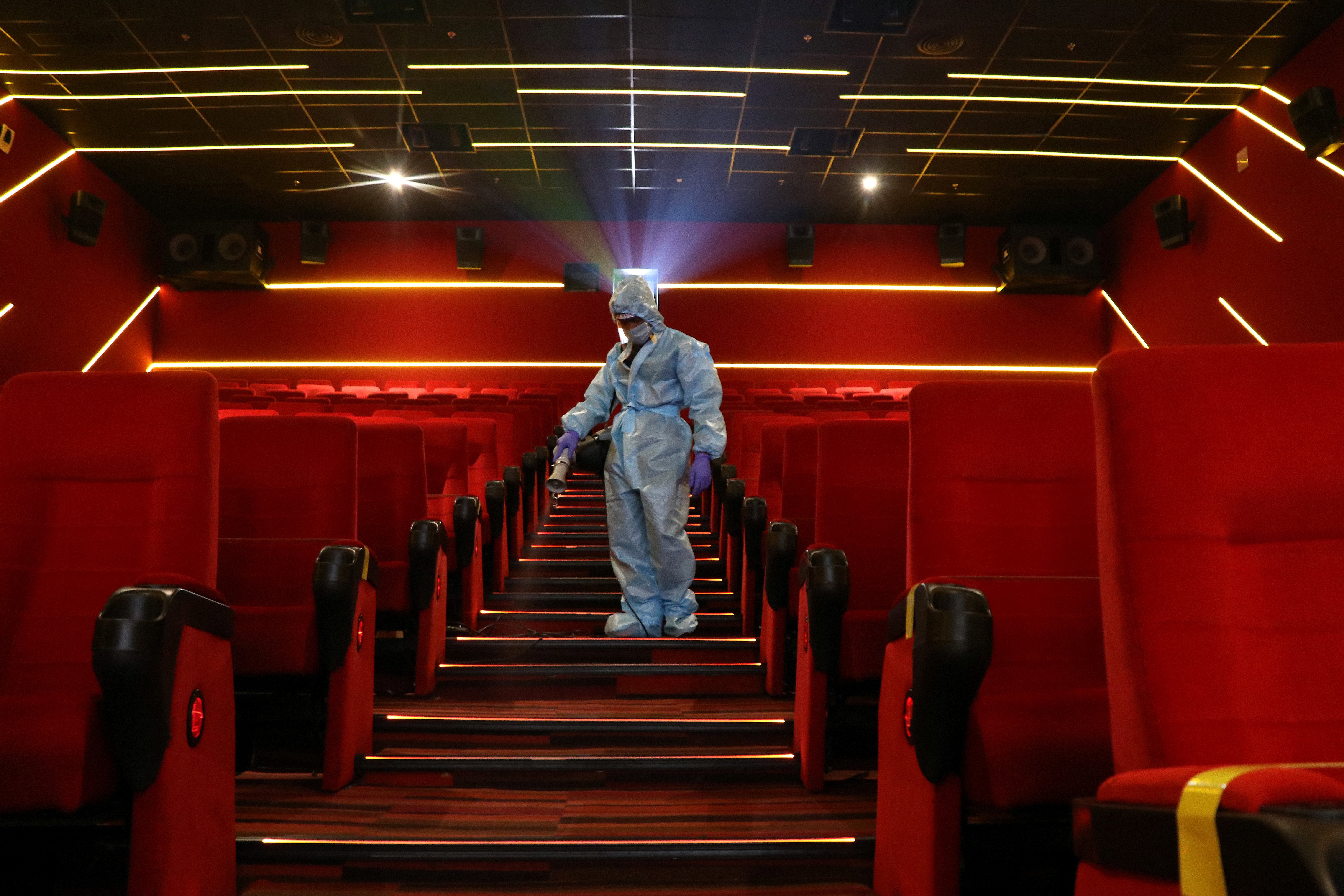 A worker wearing personal protective equipment (PPE) sanitizes seats inside the Inox Leisure movie theatre ahead of its reopening, amidst the outbreak of the coronavirus disease (COVID-19), in Mumbai, India, October 13, 2020. REUTERS/Niharika Kulkarni - RC2NHJ9WXDTJ