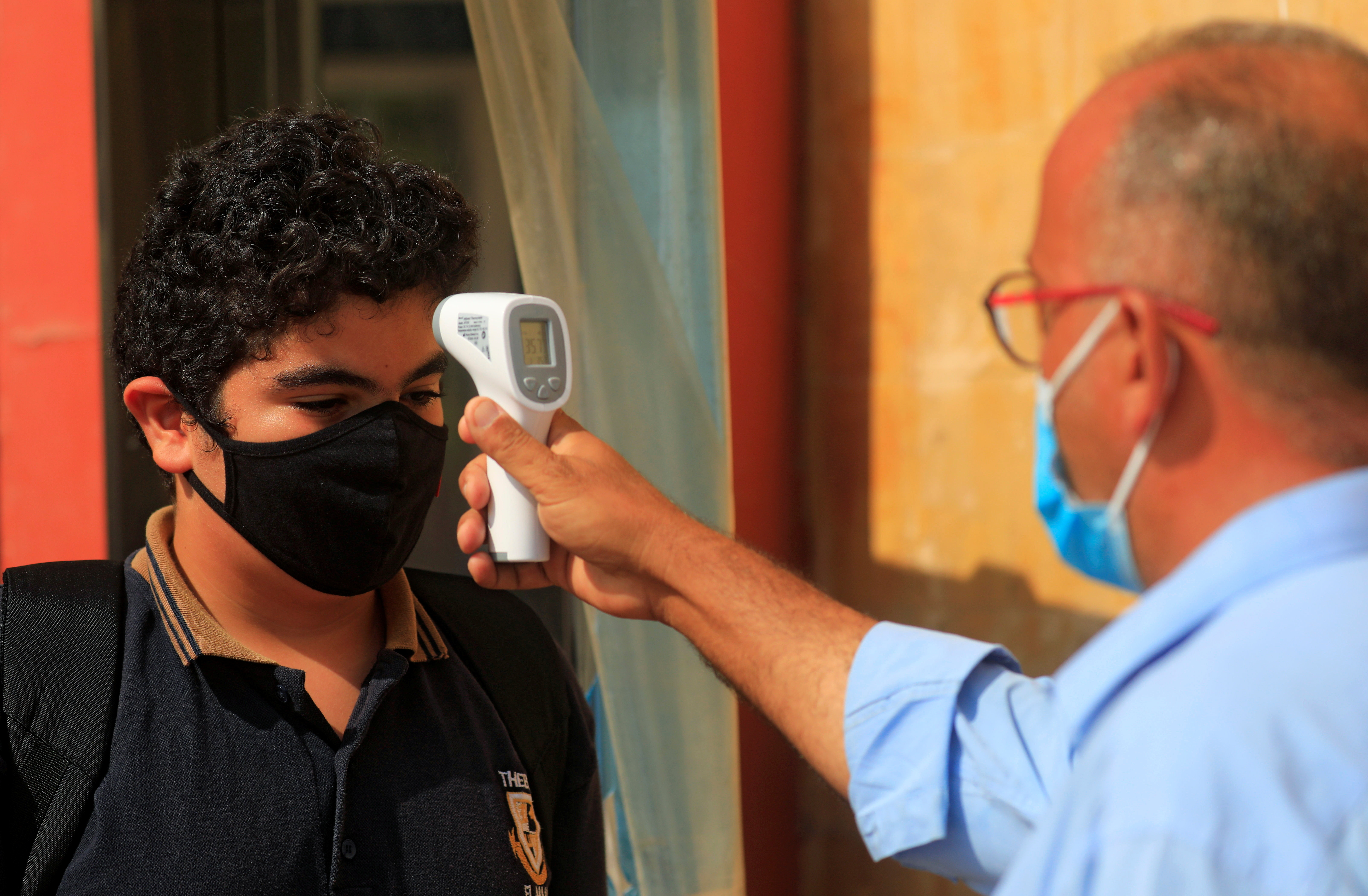 A student wearing a protective face mask has his temperature checked before entering the Tiba Maadi School, following months of closure due to the coronavirus disease (COVID-19) outbreak, in the Cairo suburb of Maadi, Egypt November 1, 2020. REUTERS/Amr Abdallah Dalsh - RC2DUJ9HFF3P