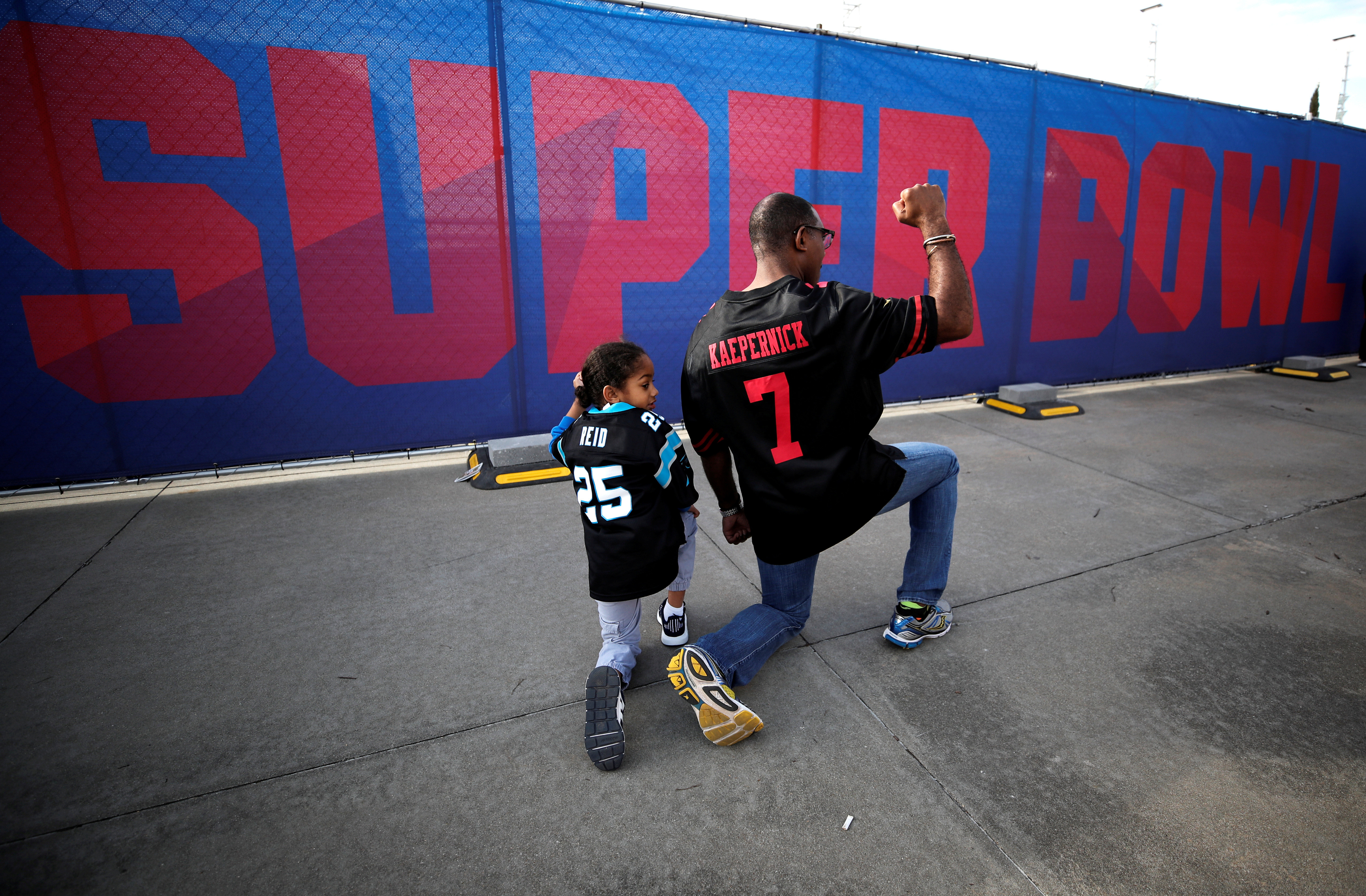 Anar Kahn from Atlanta, Georgia, kneels with his son while wearing a Colin Kaepernick football jersey outside Mercedes Benz Stadium ahead of Super Bowl LIII in Atlanta, Georgia, U.S., February 2, 2019