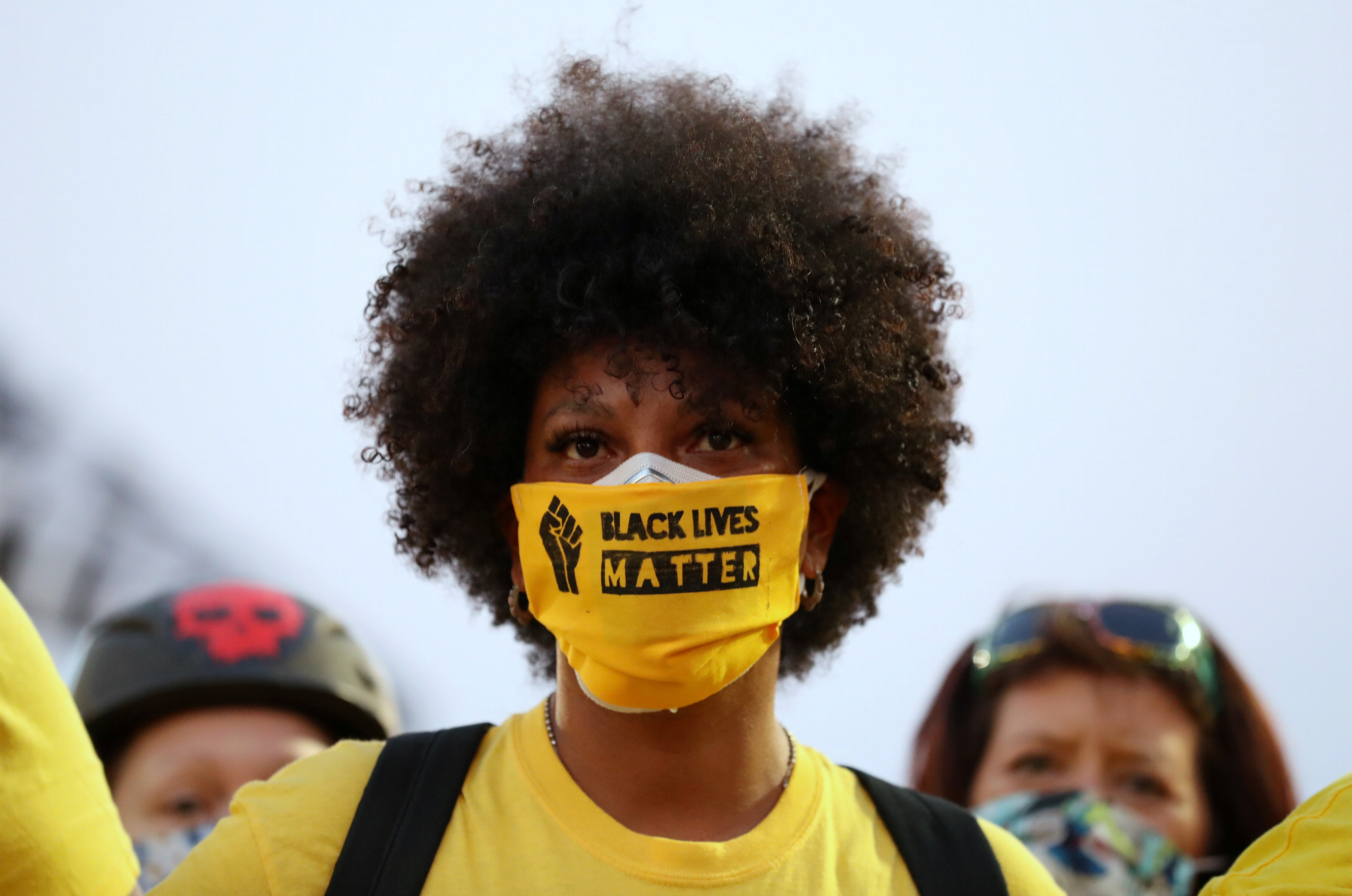 "A protester with the ""Black Lives Matter"" slogan printed on her face mask joins a protest against racial inequality and police violence in Portland, Oregon, U.S., July 26, 2020"