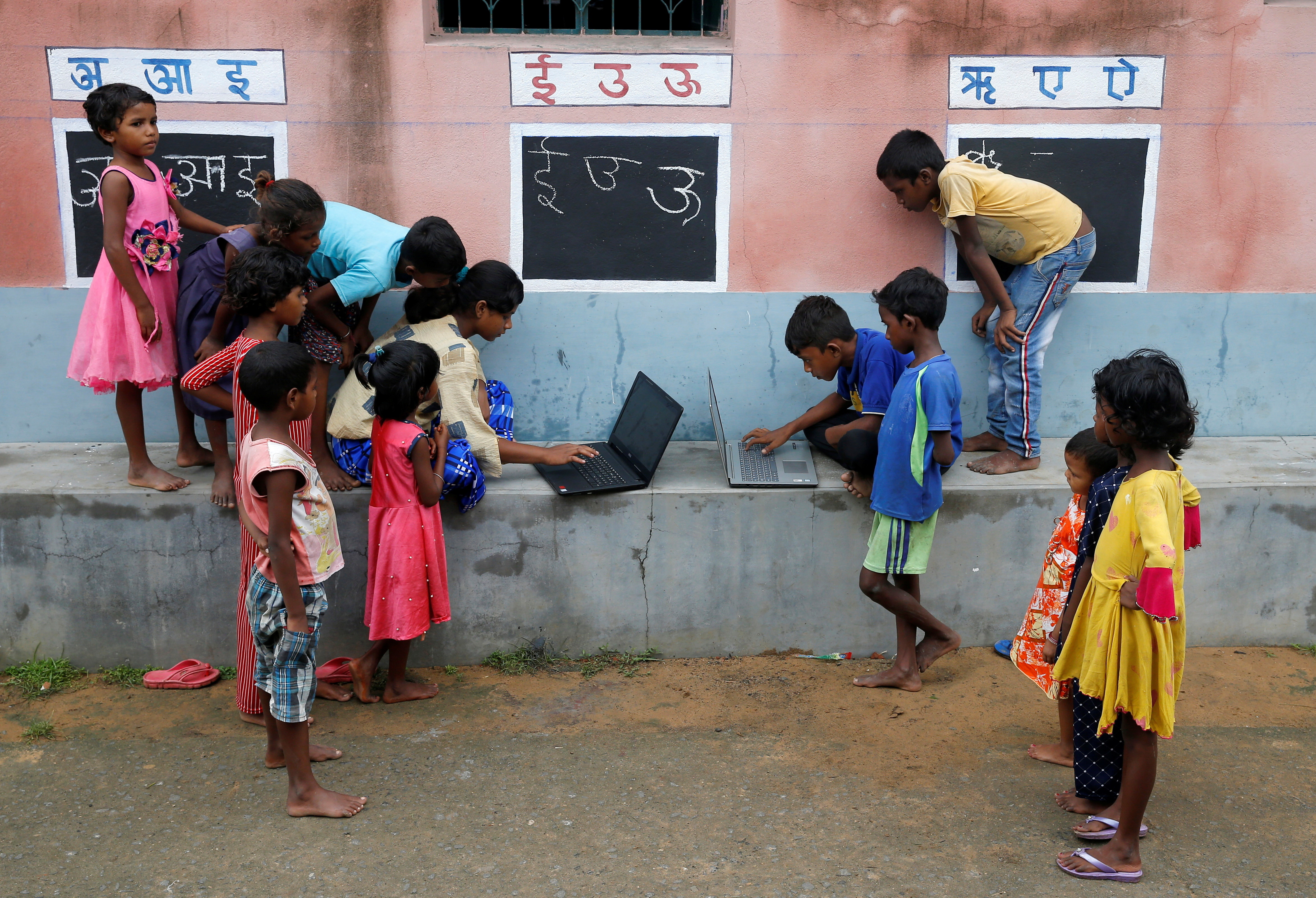 Children, who do not have access to internet facilities and gadgets, use laptops in an open-air class outside a house with the walls converted into black boards following the closure of their schools due to the coronavirus disease (COVID-19) outbreak, at Joba Attpara village in Paschim Bardhaman district in the eastern state of West Bengal, India, September 13, 2021. Picture taken September 13, 2021. REUTERS/Rupak De Chowdhuri - RC23PP98AG3Z