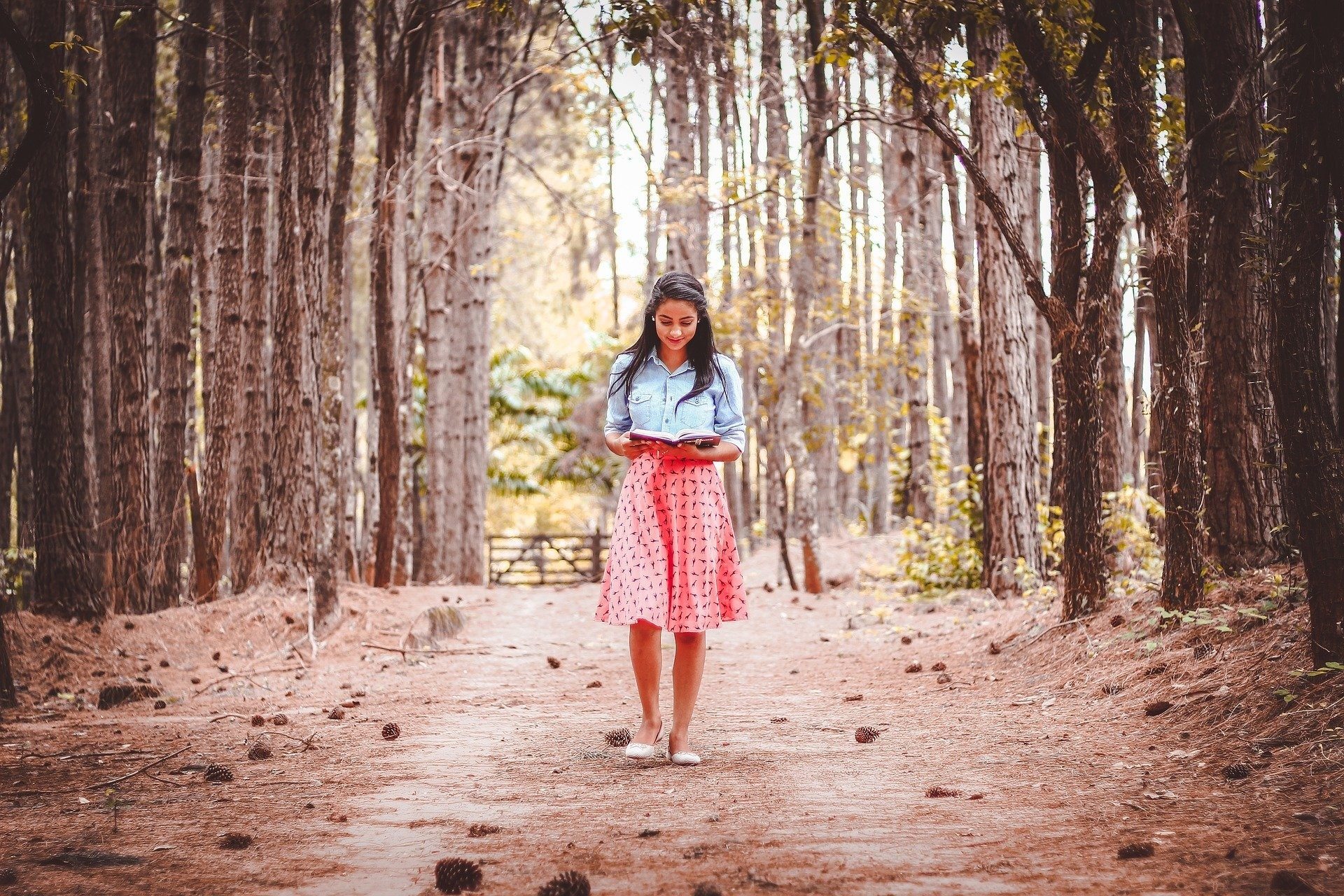 Woman reading a book as she walks in the woods
