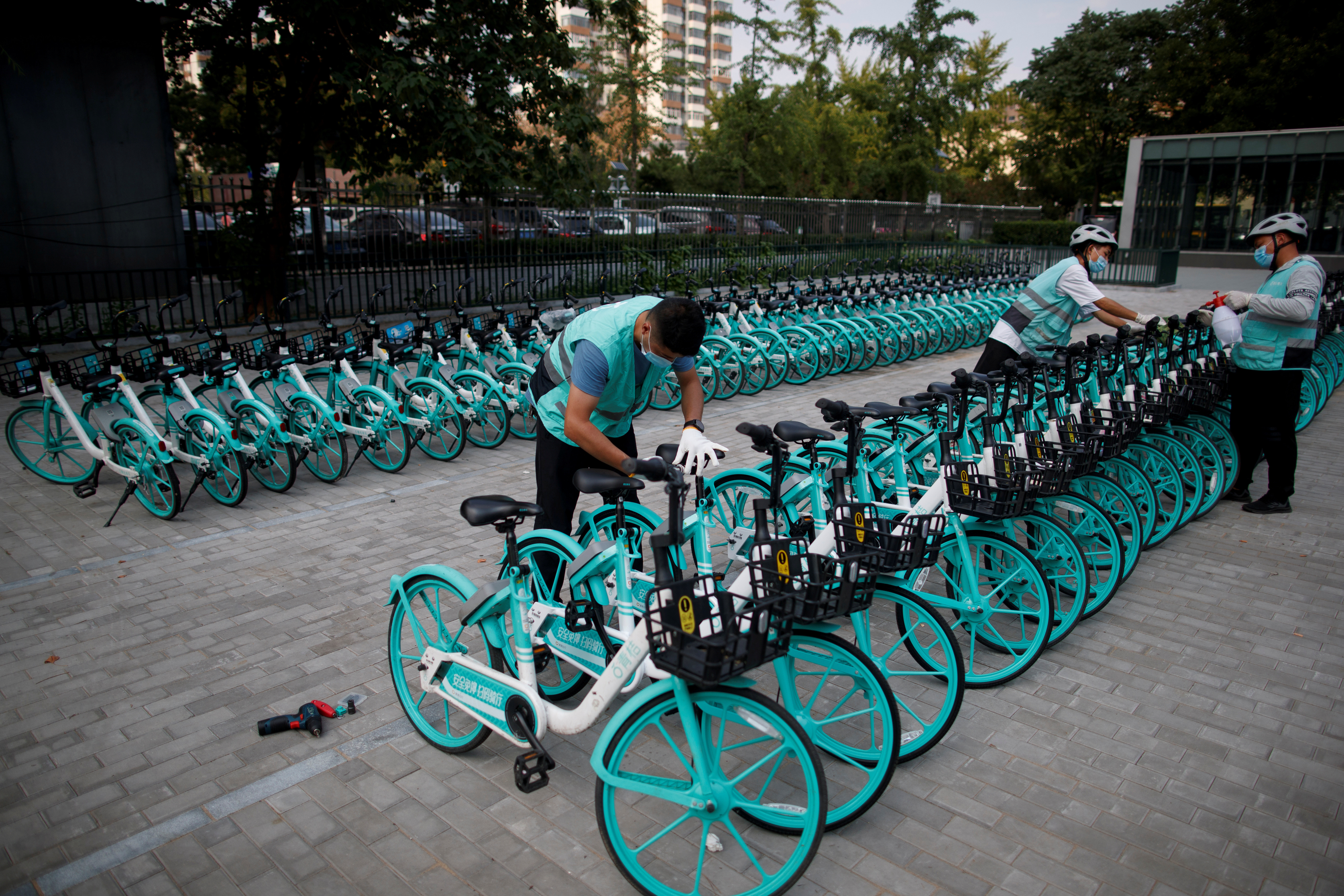 Staff members repair and disinfect Didi shared bicycles outside a subway station, following an outbreak of the coronavirus disease (COVID-19), in Beijing, China August 7, 2020. REUTERS/Thomas Peter   REFILE - REMOVING ERRONEOUS INFORMATION - RC2X8I9Y4IZA