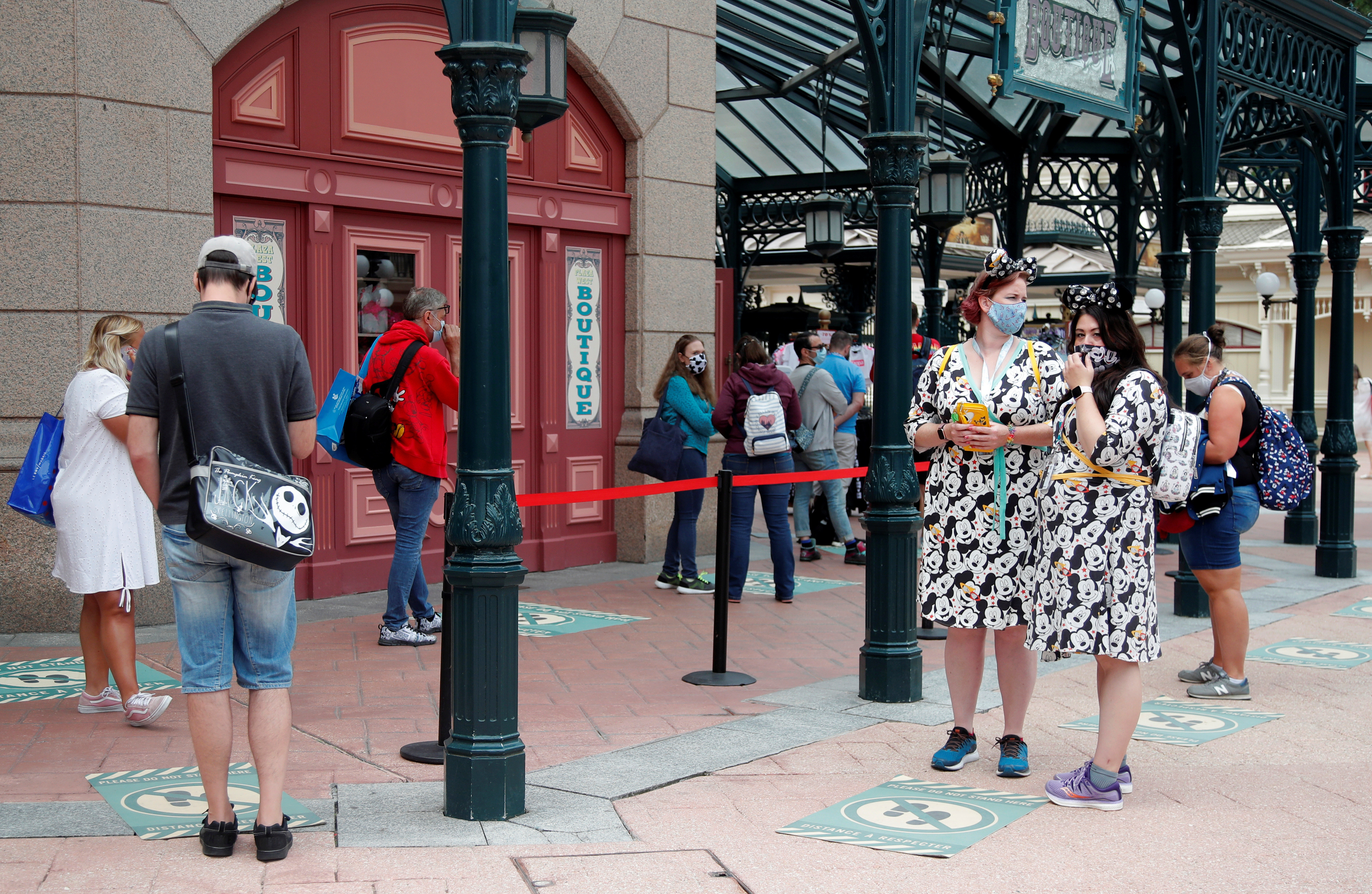 Visitors maintain social distance as they line-up at a souvenirs shop at Disneyland Paris as the theme park reopens its doors to the public in Marne-la-Vallee, near Paris, following the coronavirus disease (COVID-19) outbreak in France, July 15, 2020.   REUTERS/Charles Platiau - RC2NTH9LSY2K