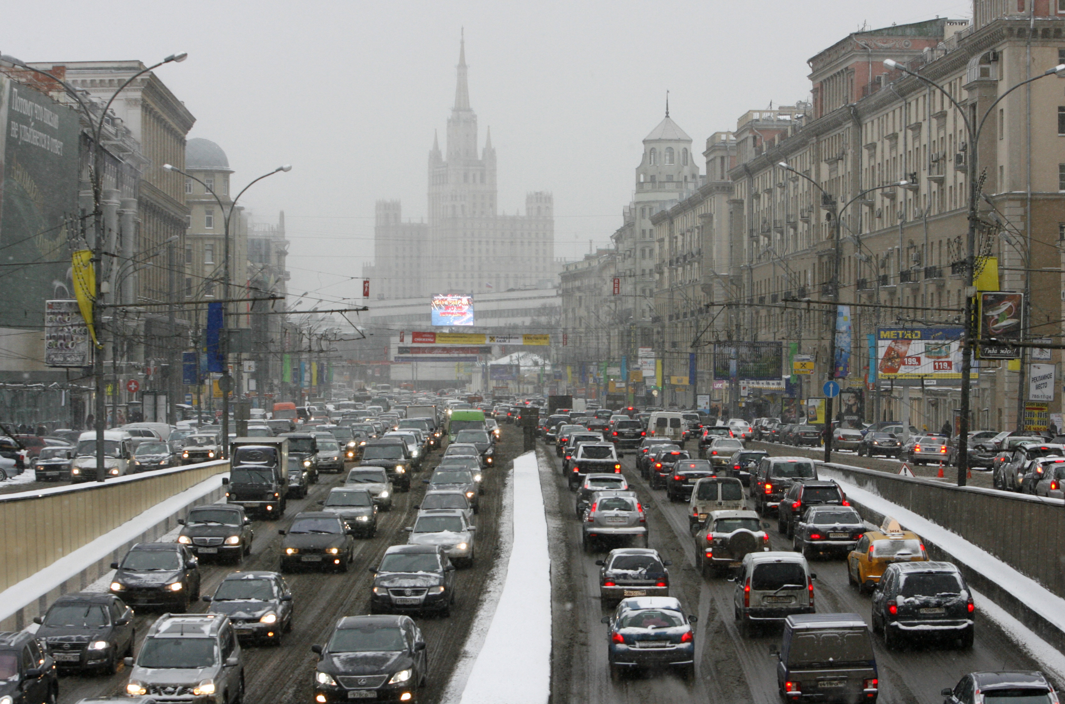 Cars move under a snowfall in central Moscow December 29, 2009.  REUTERS/Sergei Karpukhin