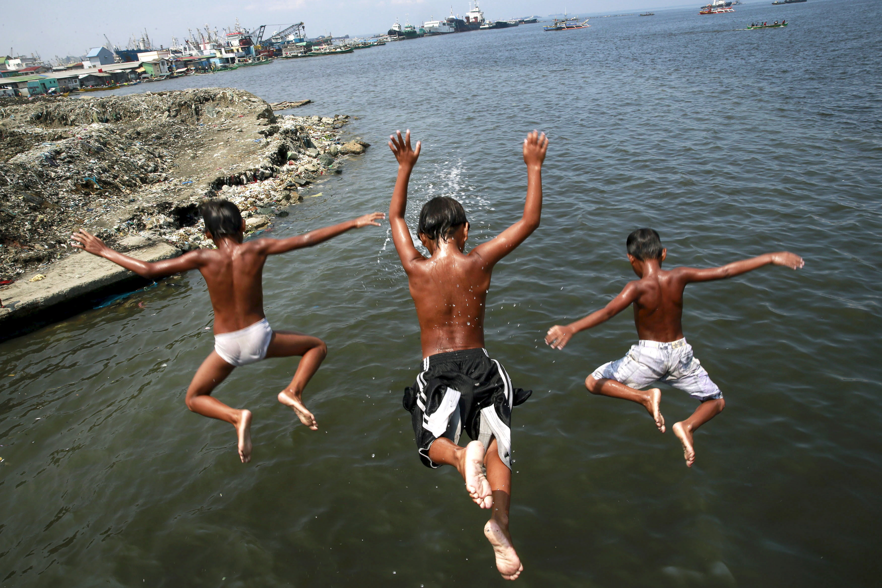 Boys dives into murky waters at a fishing town in Navotas City, north of Manila, Philippines August 4, 2015.       REUTERS/Romeo Ranoco        TPX IMAGES OF THE DAY      - GF20000012907