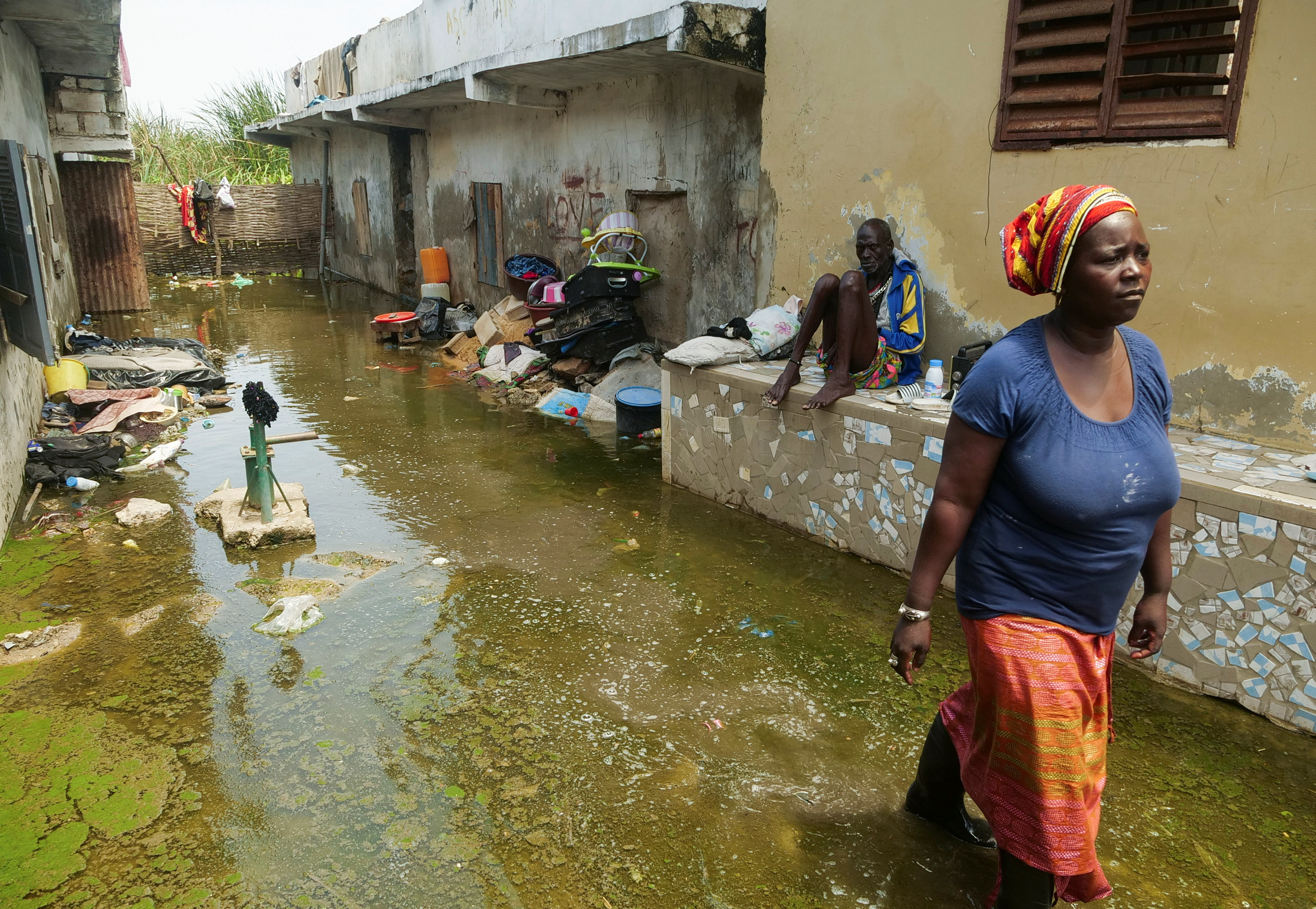 Mrs. Aicha Sy and Mr. Issa Camara, residents, are pictured in the flooded alley of their home after heavy rains in Yeumbeul district on the outskirts of Dakar, Senegal September 16, 2020. Picture taken September 16, 2020. REUTERS/Christophe Van Der Perre - RC2V4J9OM246
