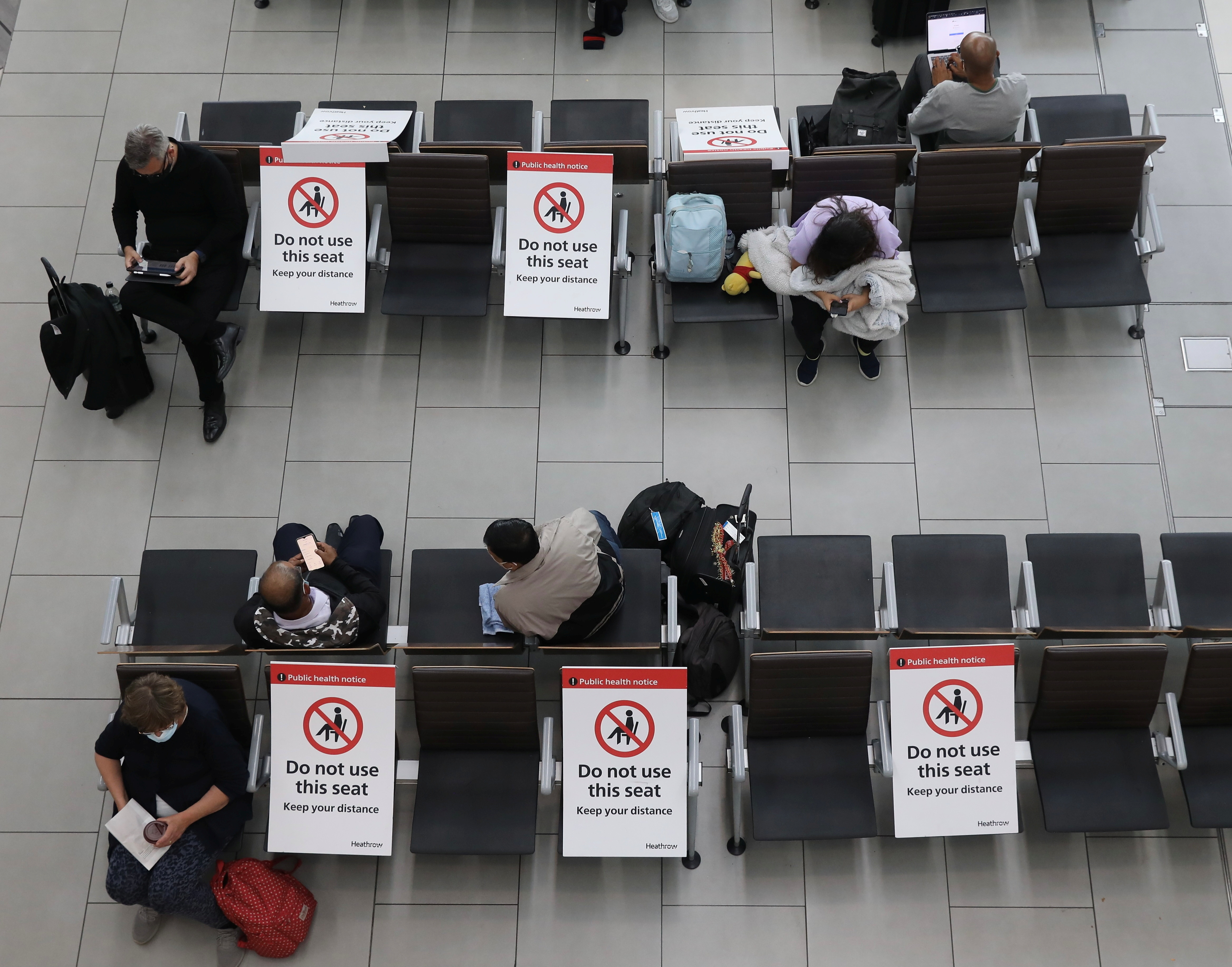 Passengers wait on socially distanced chairs at Heathrow Airport amid the coronavirus disease (COVID19) pandemic in London, Britain July 7, 2021.    REUTERS/Kevin Coombs - RC2RFO9FE2PS