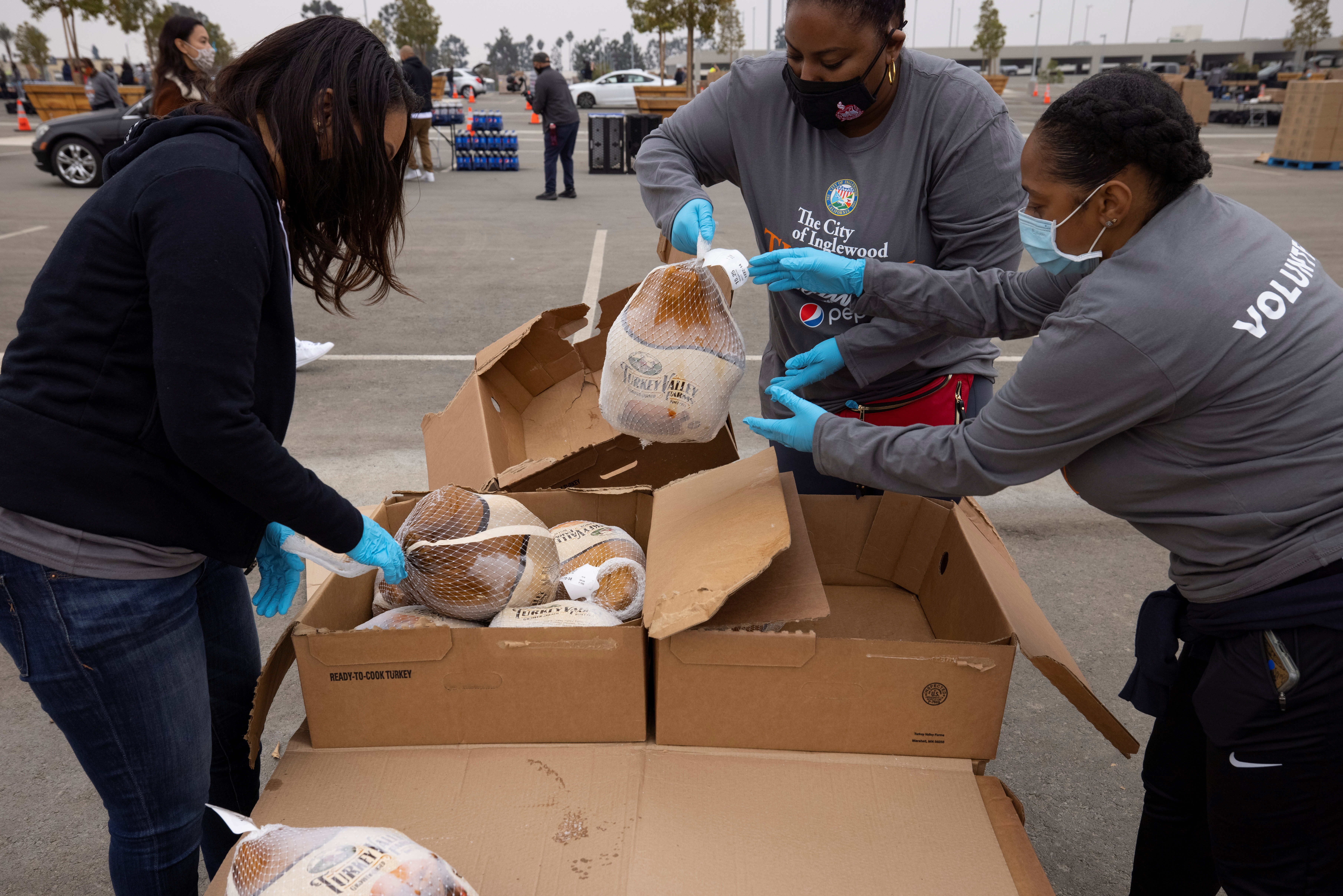 Volunteers help at the City of Inglewood's annual Thanksgiving Turkey Giveaway during the COVID-19 outbreak, in California, U.S., November 23, 2020.      REUTERS/Mike Blake - RC299K9AJOJJ