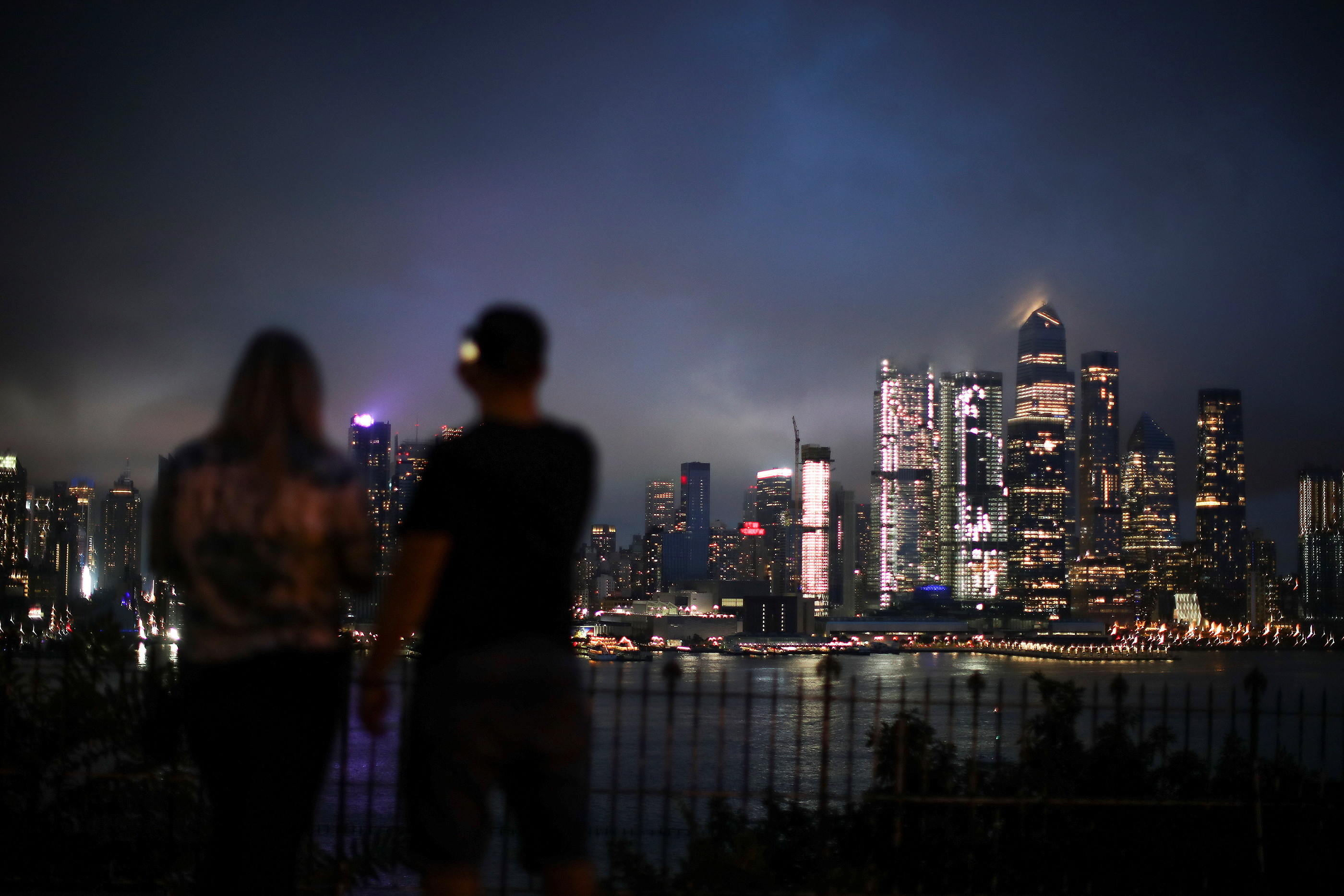People watch clouds pass over middle Manhattan and the Empire State Building as Tropical Storm Henri passes through New York City, as seen from Weehawken's Hamilton Park in New Jersey, U.S., August 18, 2021.    REUTERS/Eduardo Munoz - RC208P9G08WC