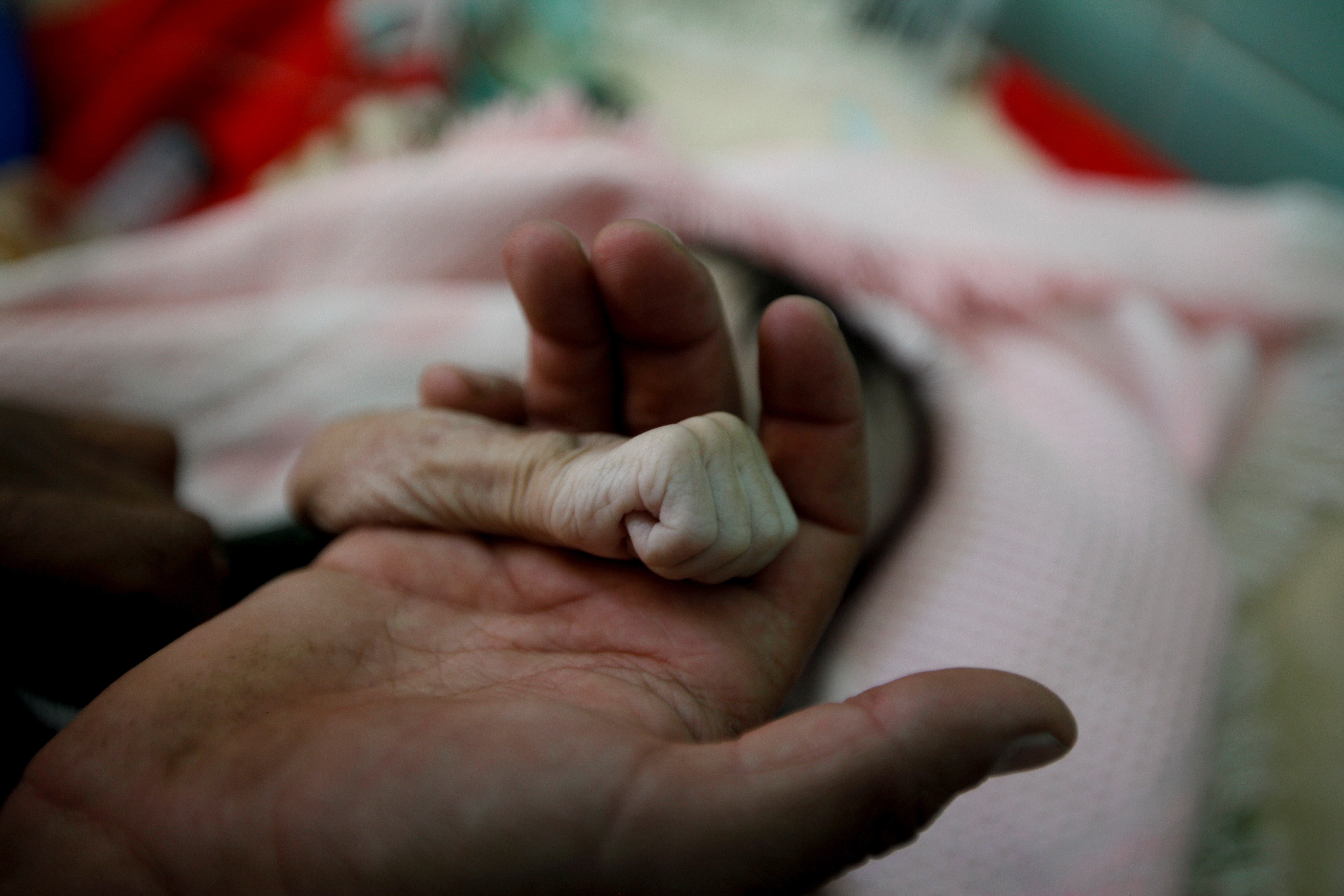"ATTENTION EDITORS - VISUAL COVERAGE OF SCENES OF INJURY OR DEATH   Saleh Hassan al-Faqeh holds the hand of his four-month-old daughter, Hajar, who died at the malnutrition ward of al-Sabeen hospital in Sanaa, Yemen, November 15, 2018. Fouad al-Reme, a nurse in al-Sabeen hospital, said Hajar was conscious when she came to the hospital but she suffered low oxygen levels. ""She was like skin on bones, her body was emaciated,"" he said. REUTERS/Mohamed al-Sayaghi   SEARCH ""MALNUTRITION HASSAN"" FOR THIS STORY. SEARCH ""WIDER IMAGE"" FOR ALL STORIES.  TPX IMAGES OF THE DAY - RC115484B0B0"