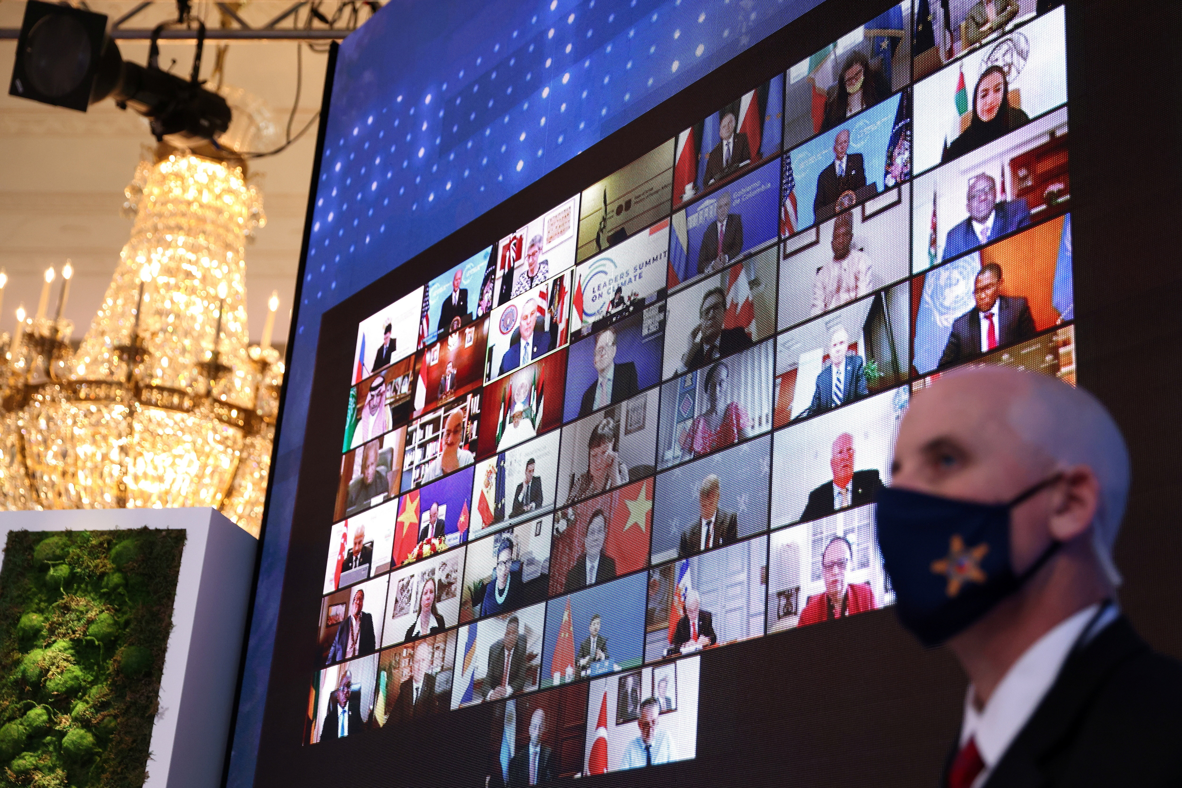 World leaders appear on a video screen during a virtual Climate Summit with world leaders in the East Room at the White House in Washington, U.S., April 23, 2021.