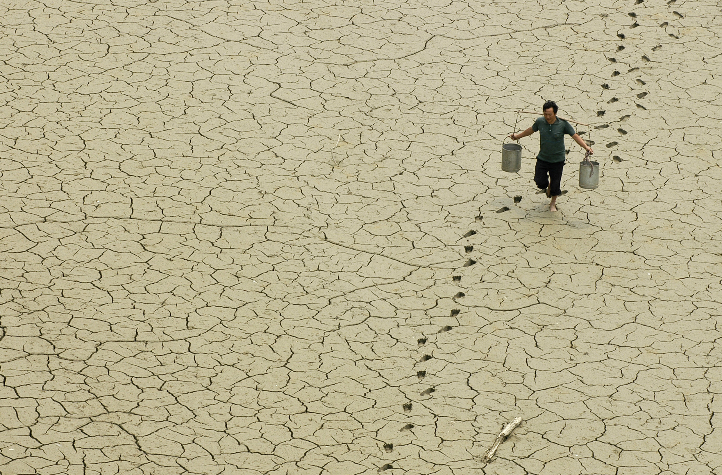 A farmer walks on a dried-up pond on the outskirts of Baokang, central China's Hubei province, June 10, 2007. REUTERS/Stringer (CHINA) CHINA OUT - GM1DVLKPZKAA