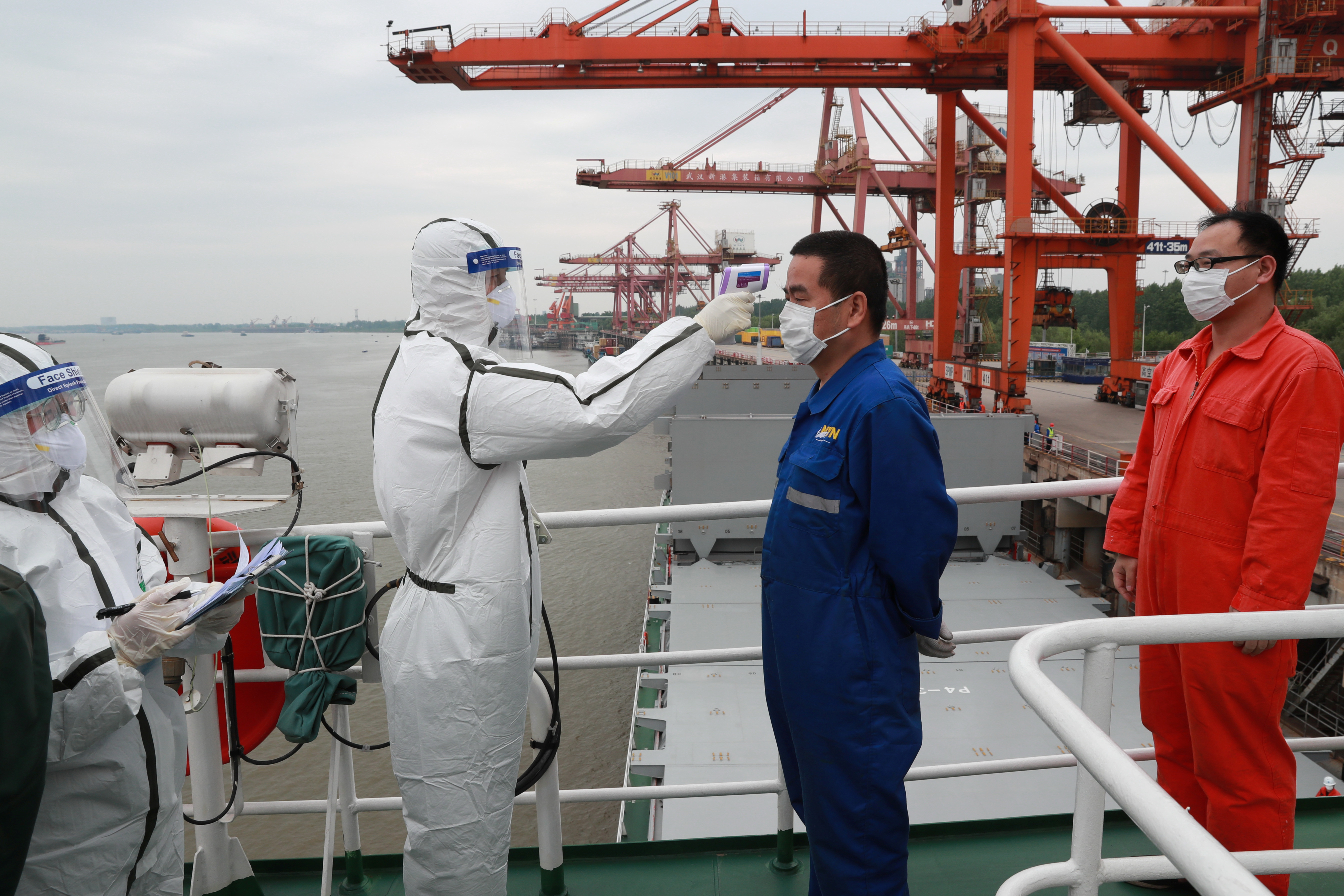 A staff member in protective suit takes body temperature measurement of a crew worker of a cargo ship bound for Japan following the coronavirus disease (COVID-19) outbreak, at a container terminal at a port in Wuhan, Hubei province, China May 9, 2020. Picture taken May 9, 2020. China Daily via REUTERS  ATTENTION EDITORS - THIS IMAGE WAS PROVIDED BY A THIRD PARTY. CHINA OUT. - RC2RMG98X0K3