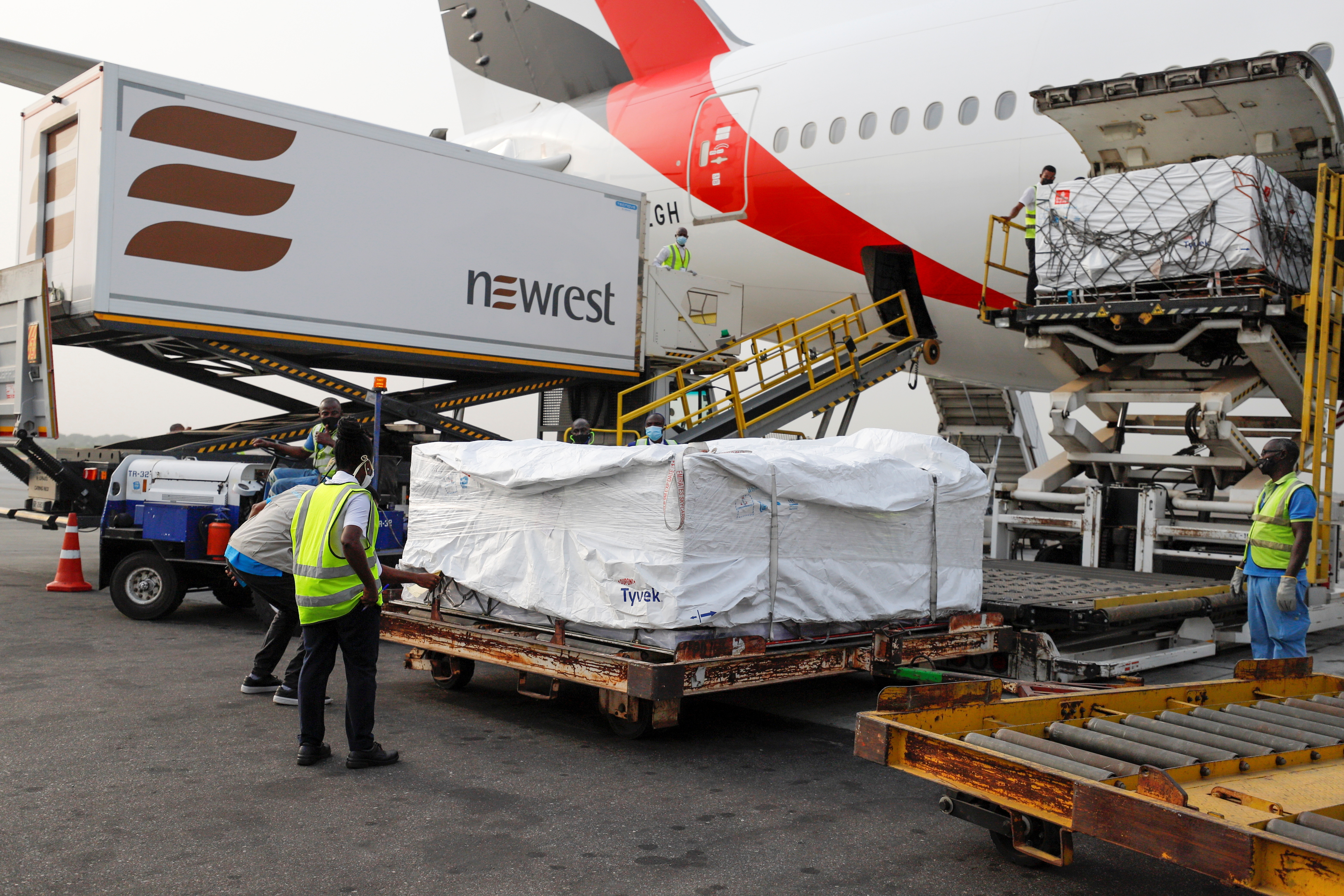 Workers offload boxes of AstraZeneca/Oxford vaccines in Ghana, the first of the COVAX vaccines to be delivered.