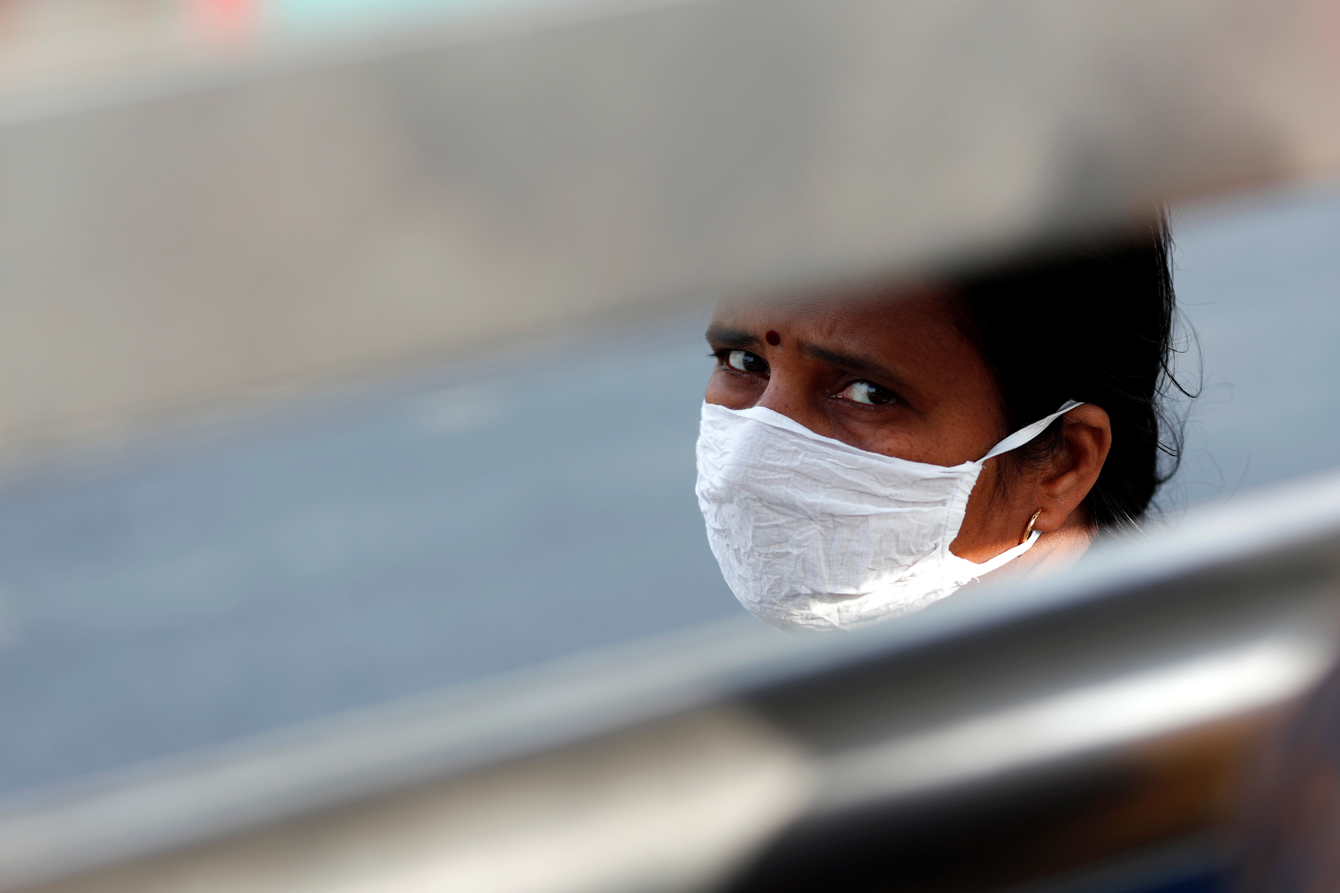 A woman wearing a protective mask waits for a bus to return to her village during lockdown by the authorities to limit the spreading of coronavirus disease (COVID-19), in New Delhi, India March 23, 2020