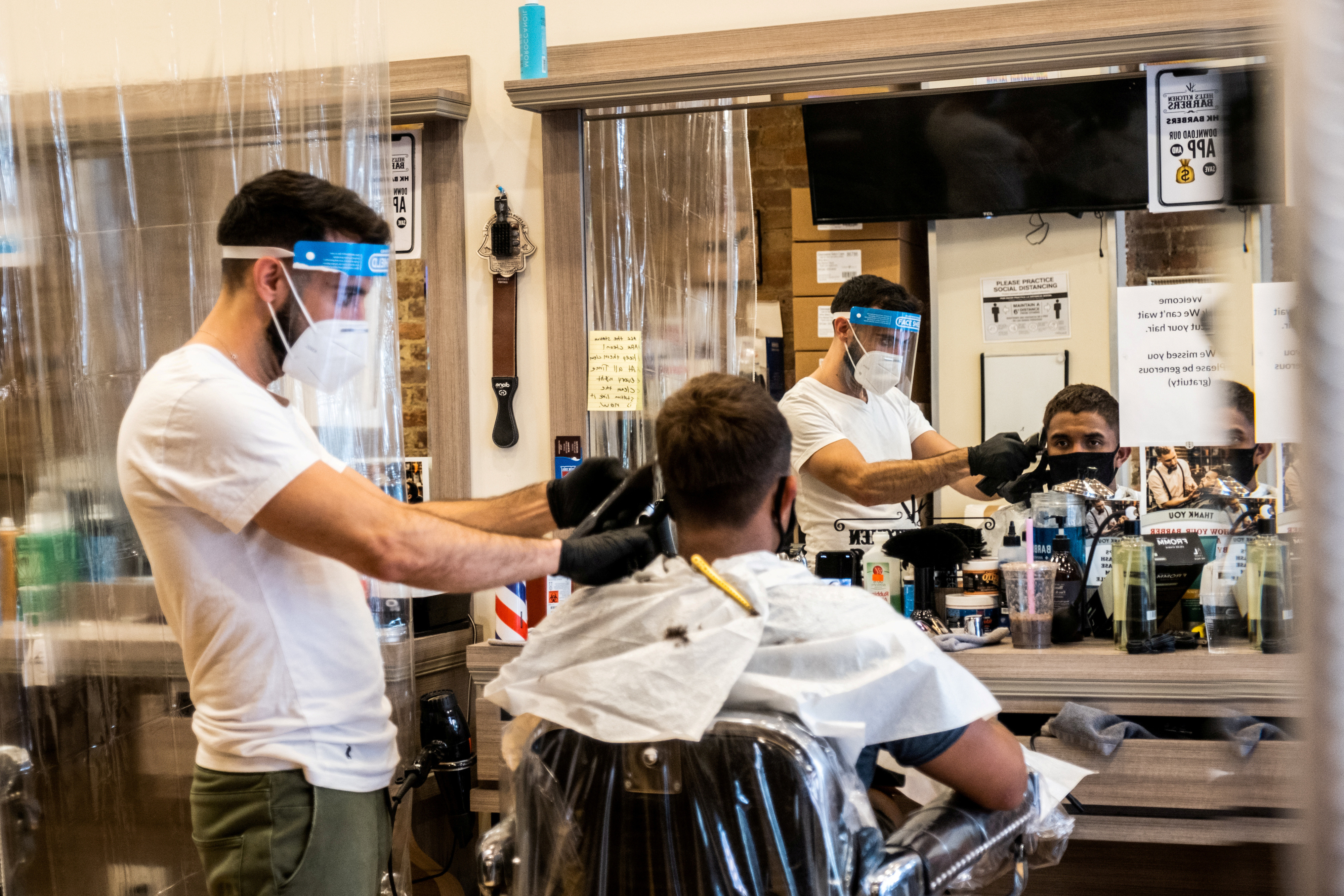 A customer wearing a face mask gets his hair cut at a barber shop after its reopening following the outbreak of the coronavirus disease (COVID-19), in New York City, New York, U.S., July 5, 2020. REUTERS/Jeenah Moon     TPX IMAGES OF THE DAY - RC2BNH9HQKQ7