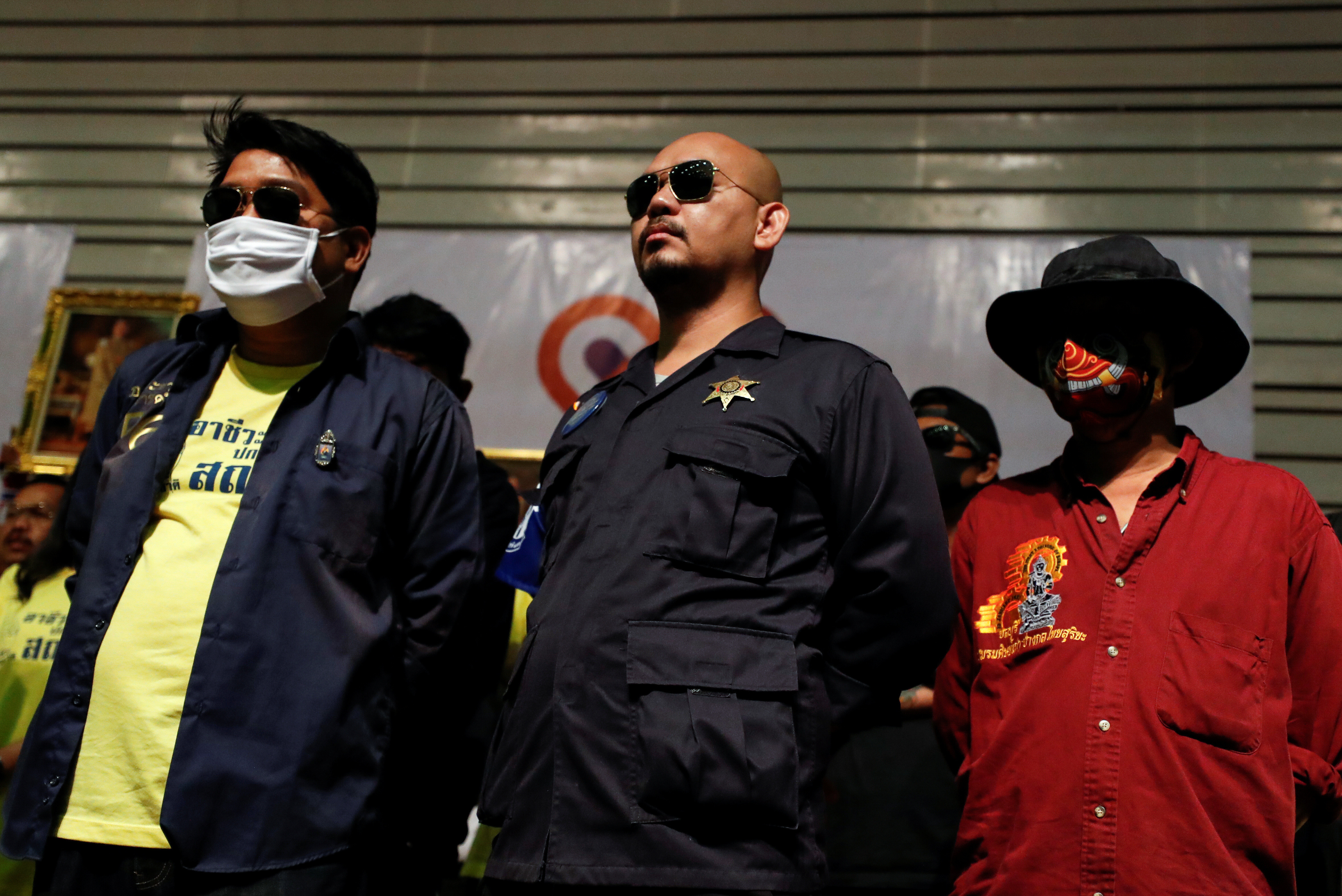"People, some wearing protective masks, look on as members of Thai right-wing group ""Thai Pakdee"" (Loyal Thai) attend a rally in support of the government and the monarchy and in opposition to the recent anti-government protests, in Bangkok, Thailand August 30, 2020. REUTERS/Jorge Silva - RC2AOI9LOBU1"
