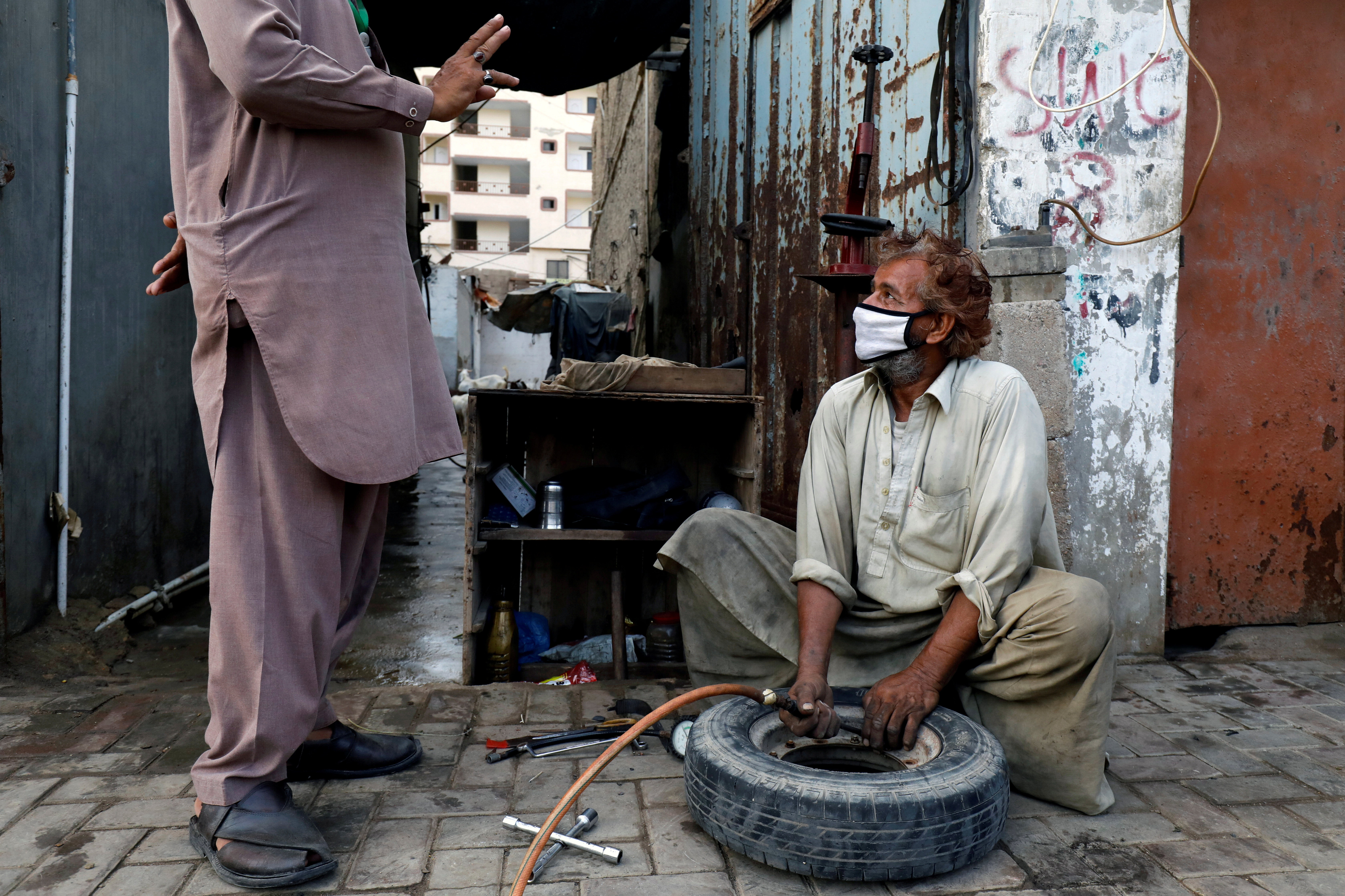 A labourer wearing protective face mask fills air in a tyre at a workshop along a road.
