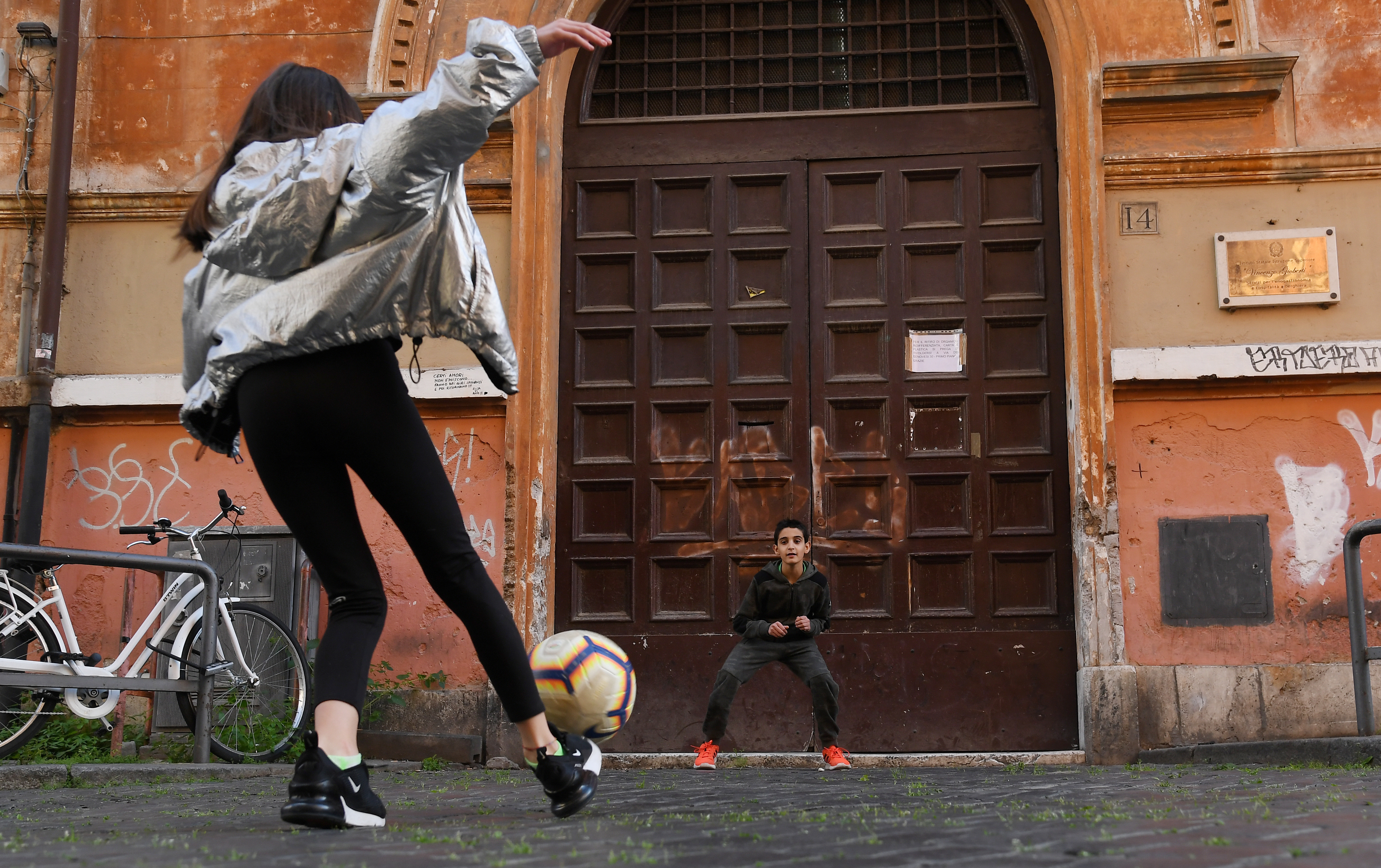 Children play football on the streets of Rome, amid the spread of coronavirus disease (COVID-19) continues in Rome, Italy, April 23, 2020.