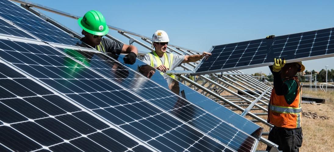 Three men install solar panels.