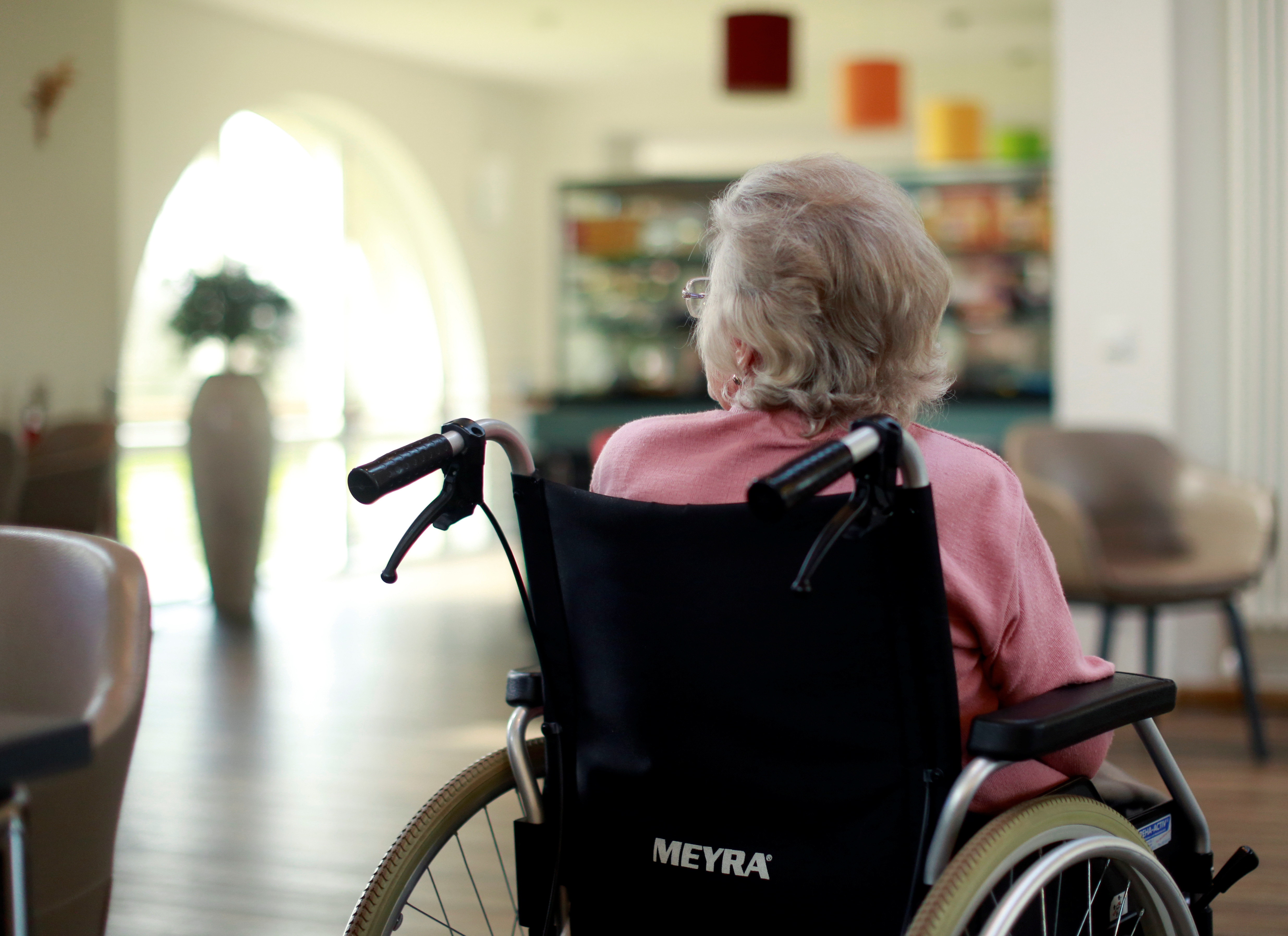 An elderly woman sits in the recreation room of a retirement home as visits have been restricted due to the coronavirus disease (COVID-19) concerns in Grevenbroich, Germany, March 16, 2020.