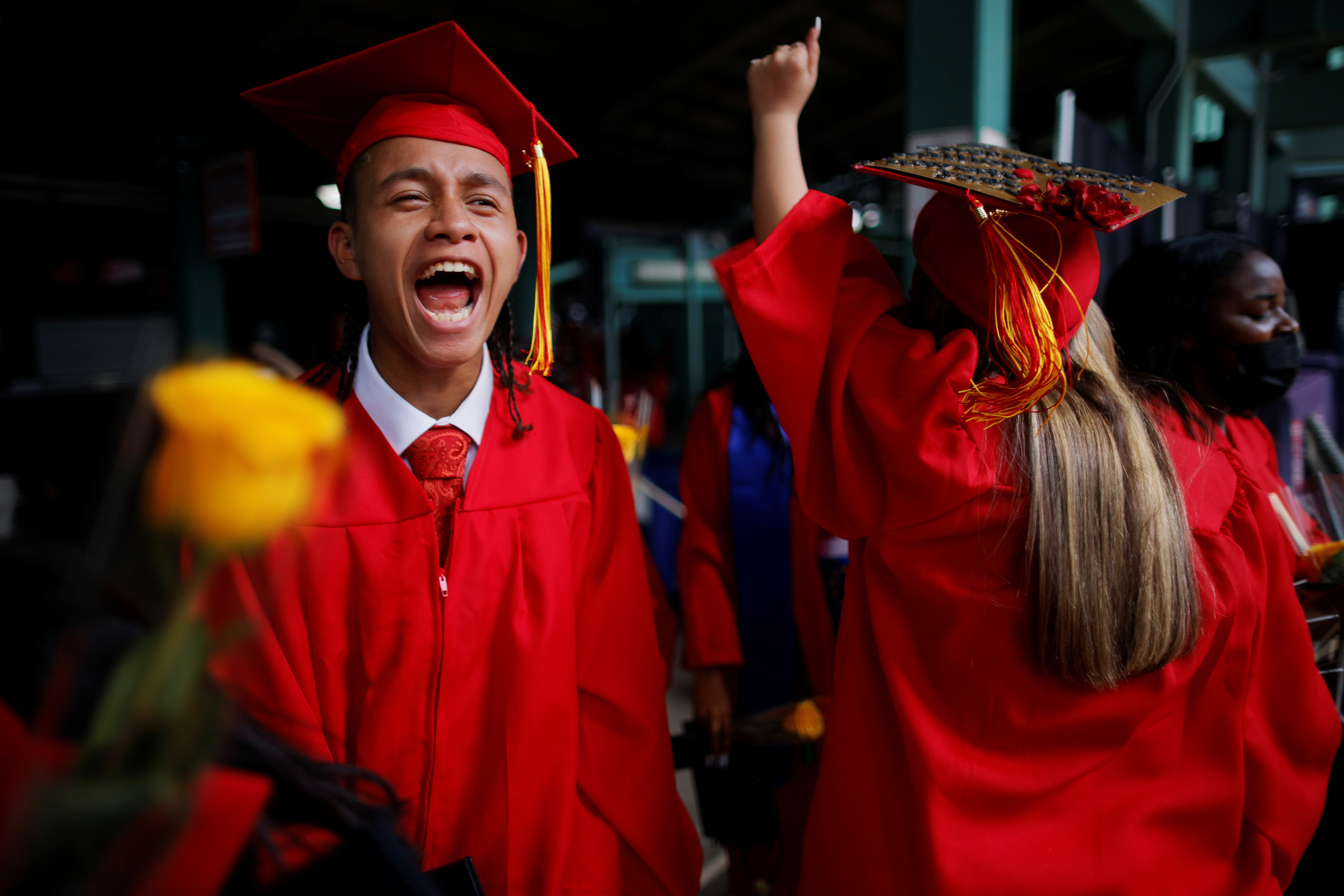 High school seniors celebrate after receiving their diploma in mortar boards