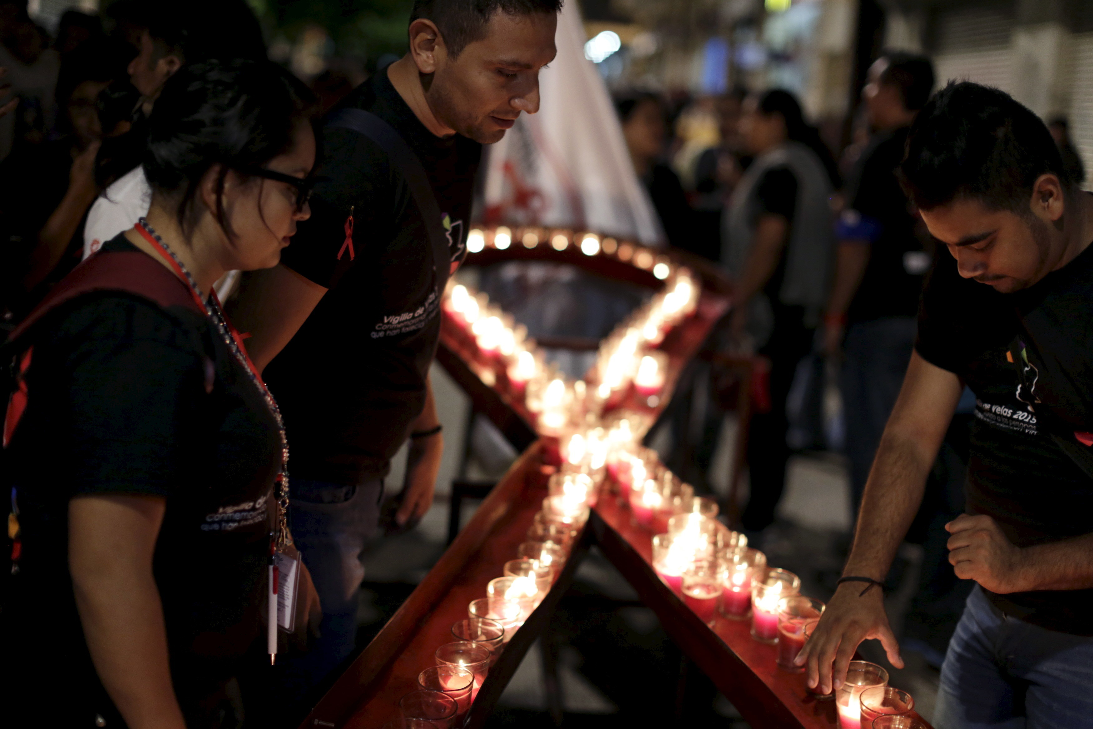 "People place candles in the shape of an HIV/AIDS awareness ""Red Ribbon"" during the ""Candlelight Memorial"" in downtown Guatemala City, May 17, 2015. The Candlelight Memorial is an annual social mobilization campaign to inform, educate and raise awareness in the general population about HIV, according to the organizers.   REUTERS/Jorge Dan Lopez - GF10000098792"