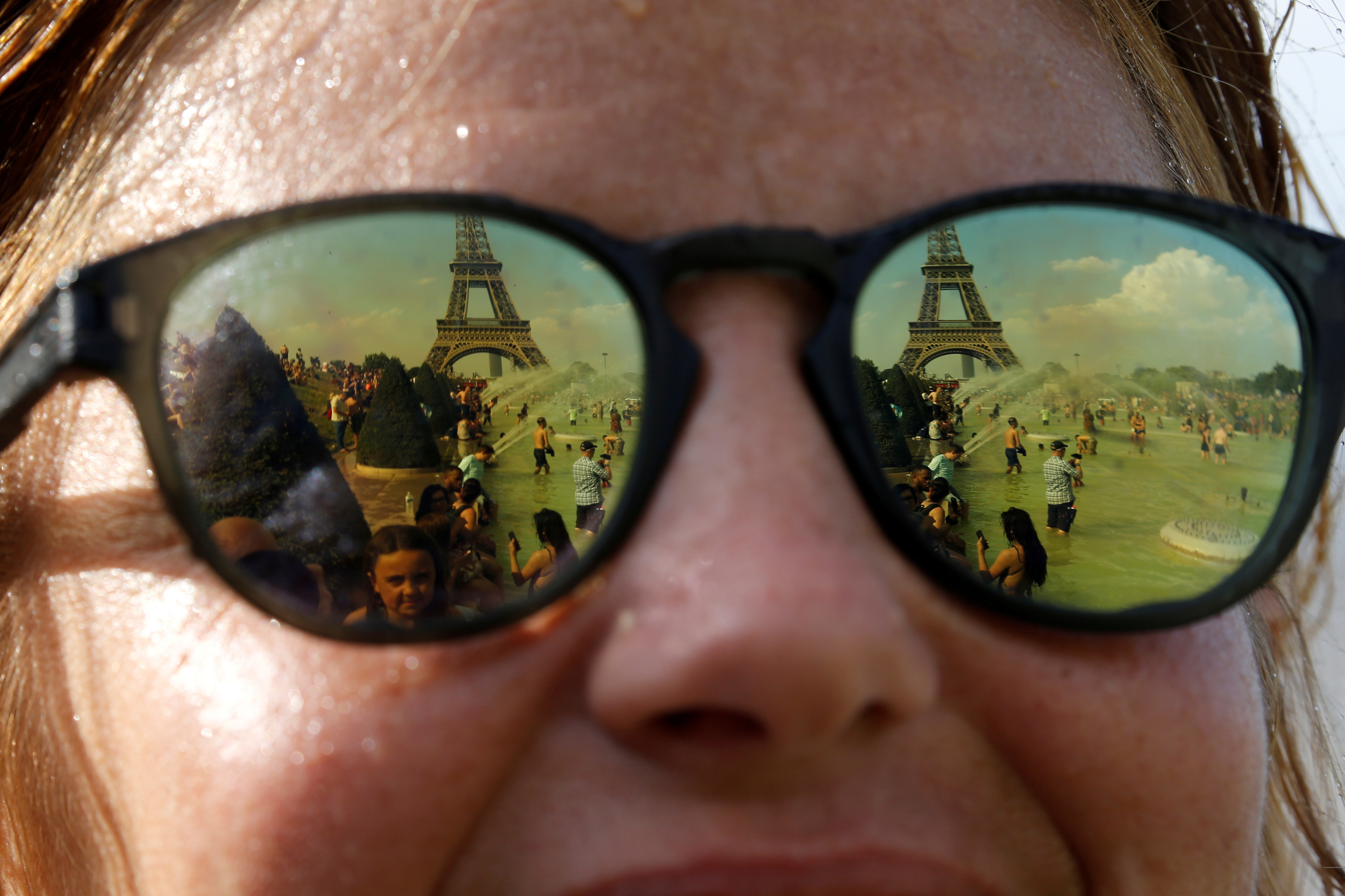 People cooling off in the Trocadero fountains across from the Eiffel Tower are reflected in sunglasses in Paris as a new heatwave broke temperature records in France