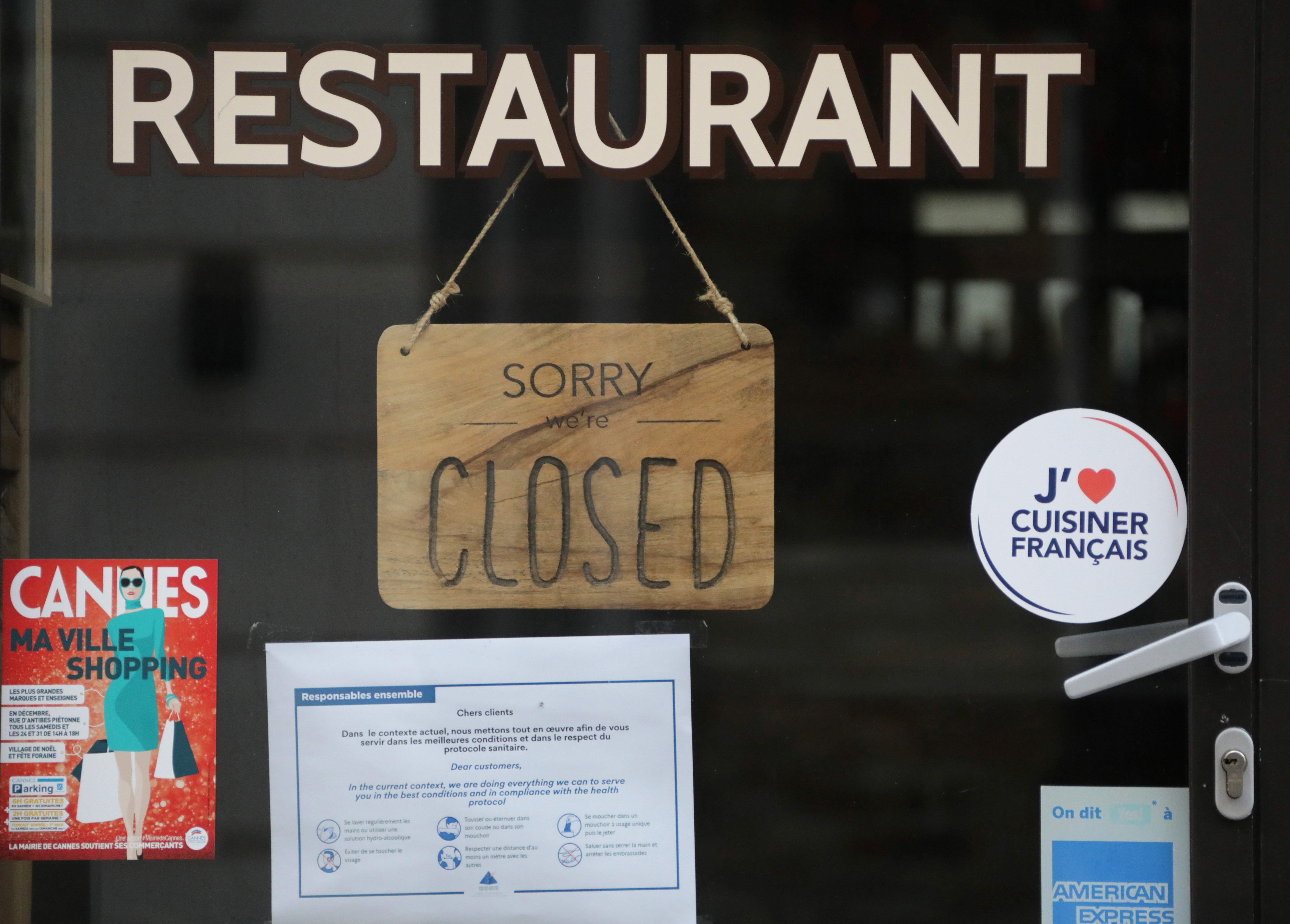 """A sign reading """"Sorry, we are closed"""" is seen on a closed restaurant in Cannes as the French government keeps bars and restaurants closed as part of COVID-19 restrictions measures to fight the coronavirus disease outbreak in France, January 11, 2021. REUTERS/Eric Gaillard - RC2S5L9ZJ0J1"""