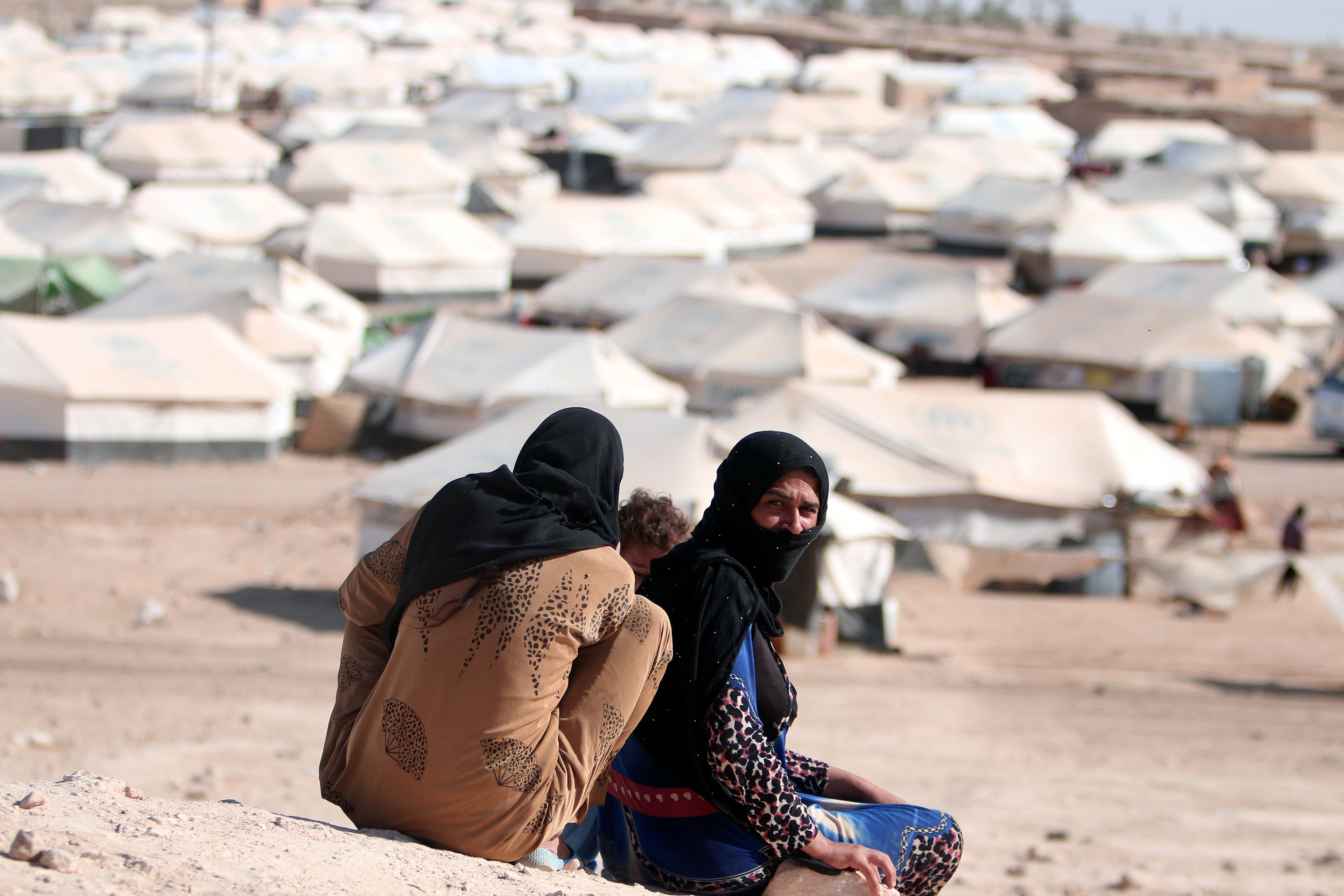 Iraqi refugee women sit overlooking al-Howl refugee camp south of Hasaka city, Syria October 20, 2016.