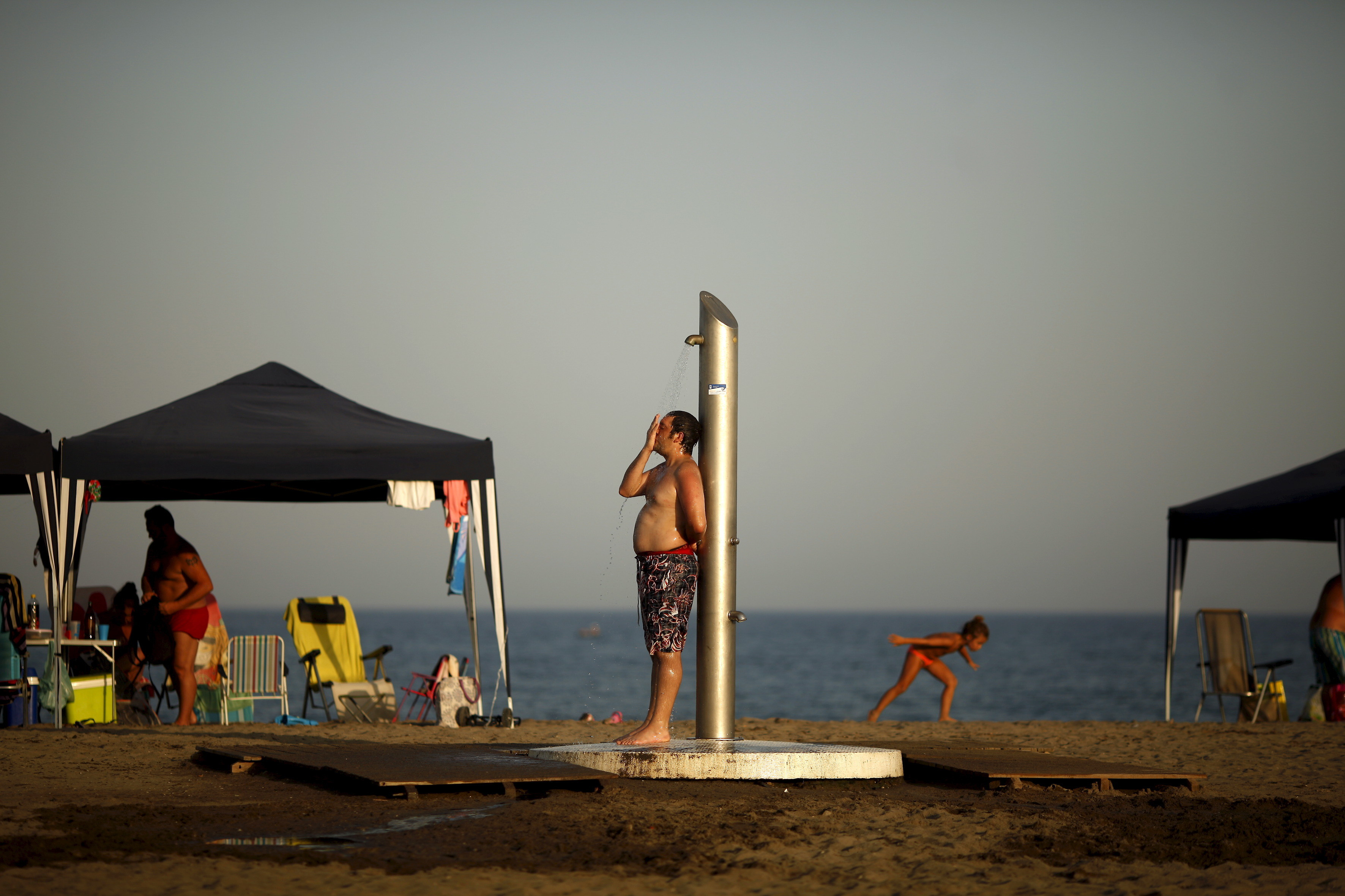 "A man takes a shower during the second heat wave of the summer on Sacaba beach in Malaga, southern Spain, July 5, 2015. As Germany and Spain sweated and London sweltered through its hottest July day on record this week, scientists said it is ""virtually certain"" that climate change is increasing the likelihood of such heat waves in Europe. Temperatures will rise up to 44 degrees Celsius (111.2 fahrenheit) in some parts of Spain and will continue during a week, the Spanish Agency of Meteorology (AEMET) said on Thursday. REUTERS/Jon Nazca - GF10000149506"