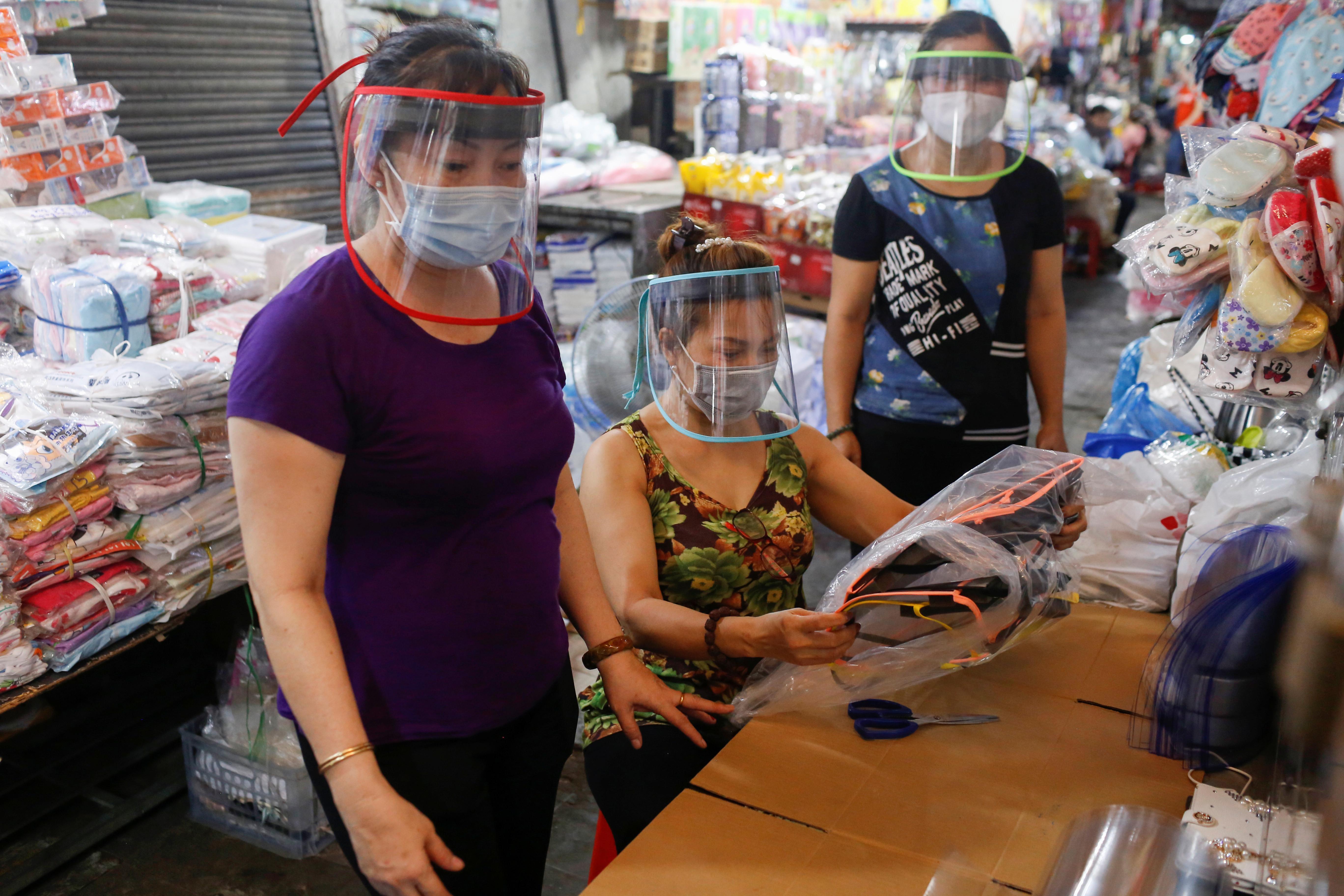Las vendedoras del mercado de Ba Chieu usan las máscaras de plástico que ayudaron a hacer durante el brote de la enfermedad coronavirus (COVID-19), en Ho Chi Minh, Vietnam, el 4 de abril de 2020.