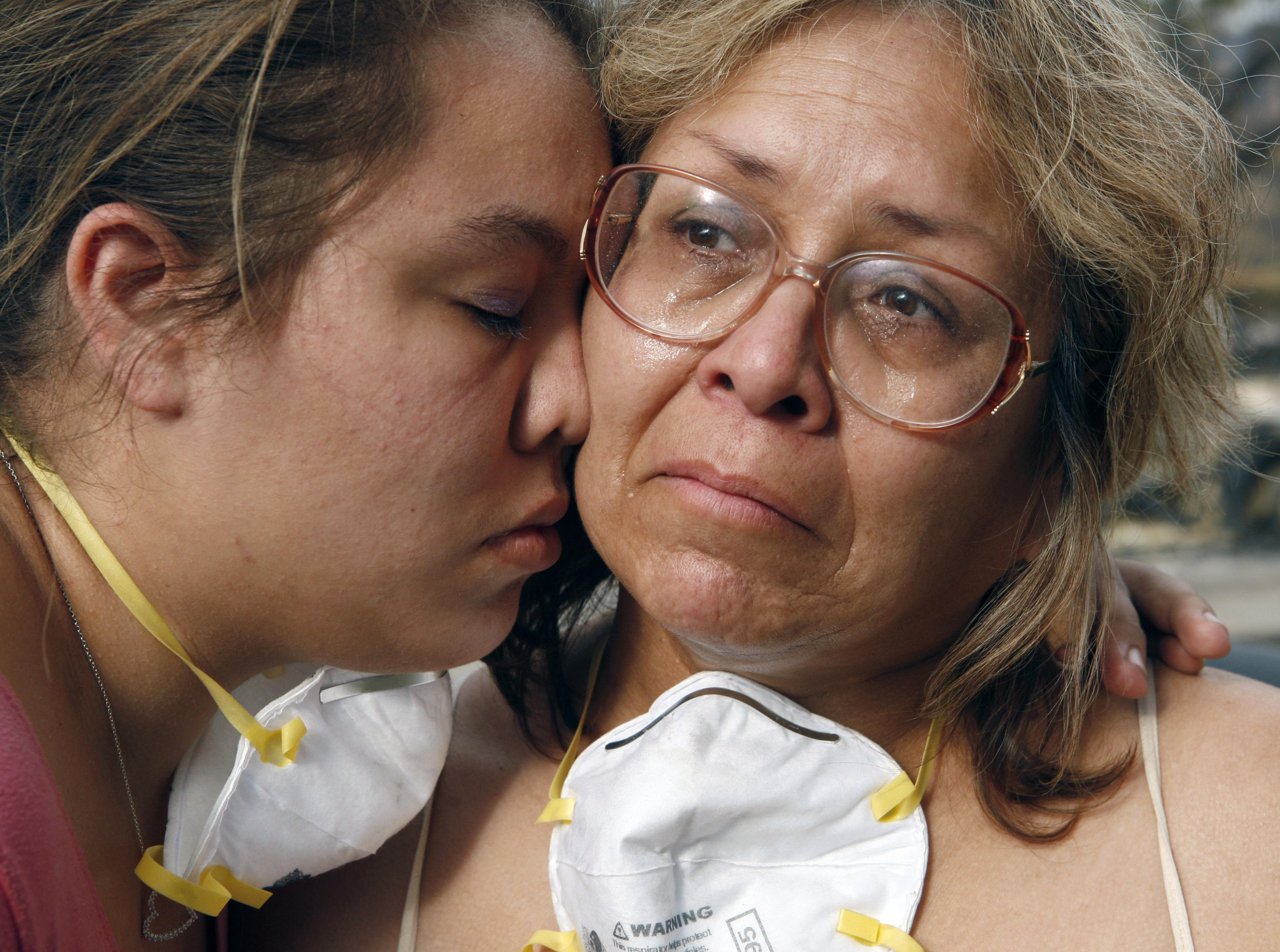 Lori Hutter (R) cries with her daughter Cassie next to their burned out home in the Rancho Bernardo neighborhood of San Diego, California October 27, 2007. Risk Management Solutions, which predicts and assesses insured damages, said in a statement that the wildfires which have devastated Southern California would likely cost insurers between $900 million and $1.6 billion. REUTERS/John Gress (UNITED STATES) - GM1DWLUTSGAA
