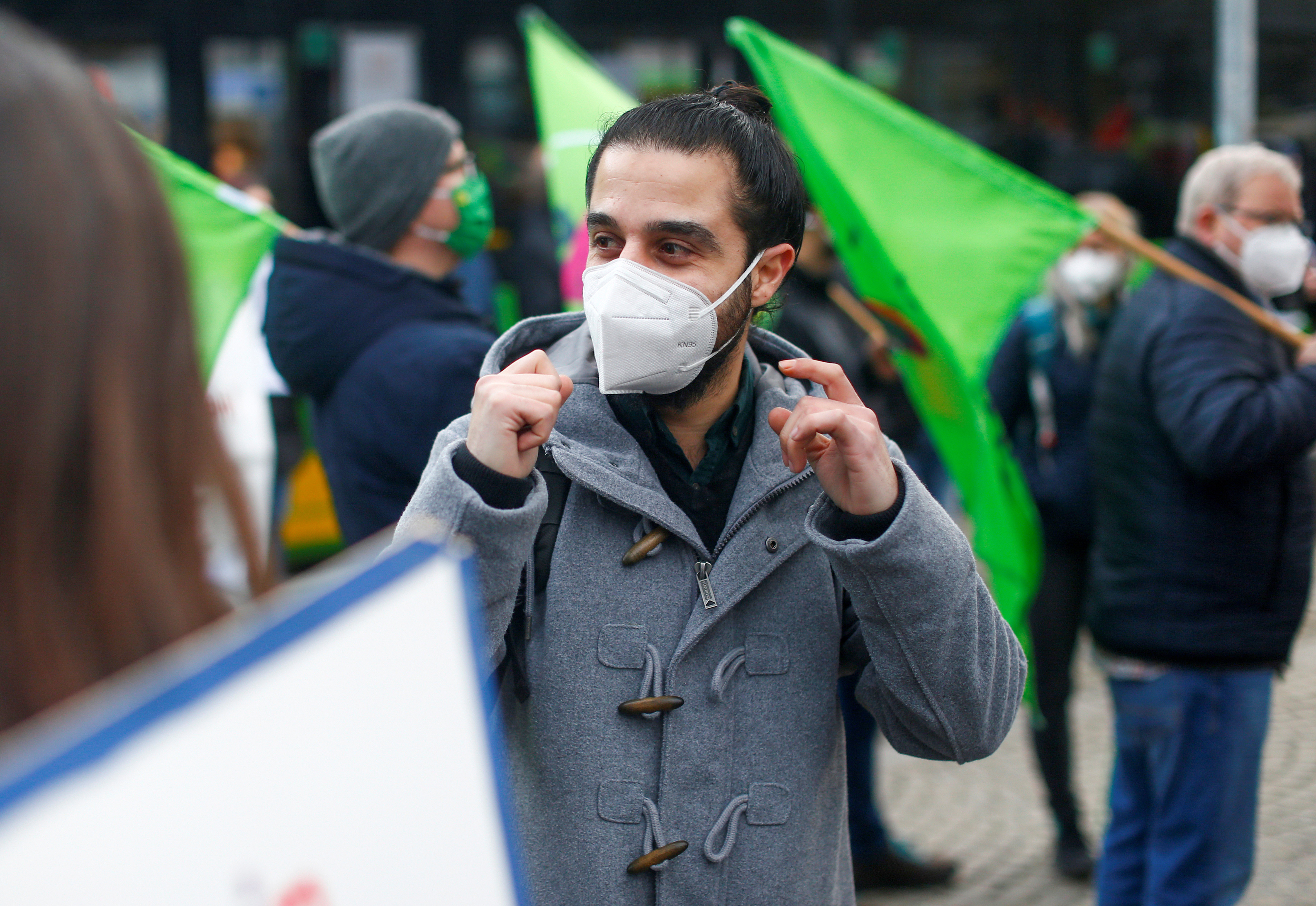 a picture of Syrian migrant Tareq Alaows with a protective face mask on out campaigning