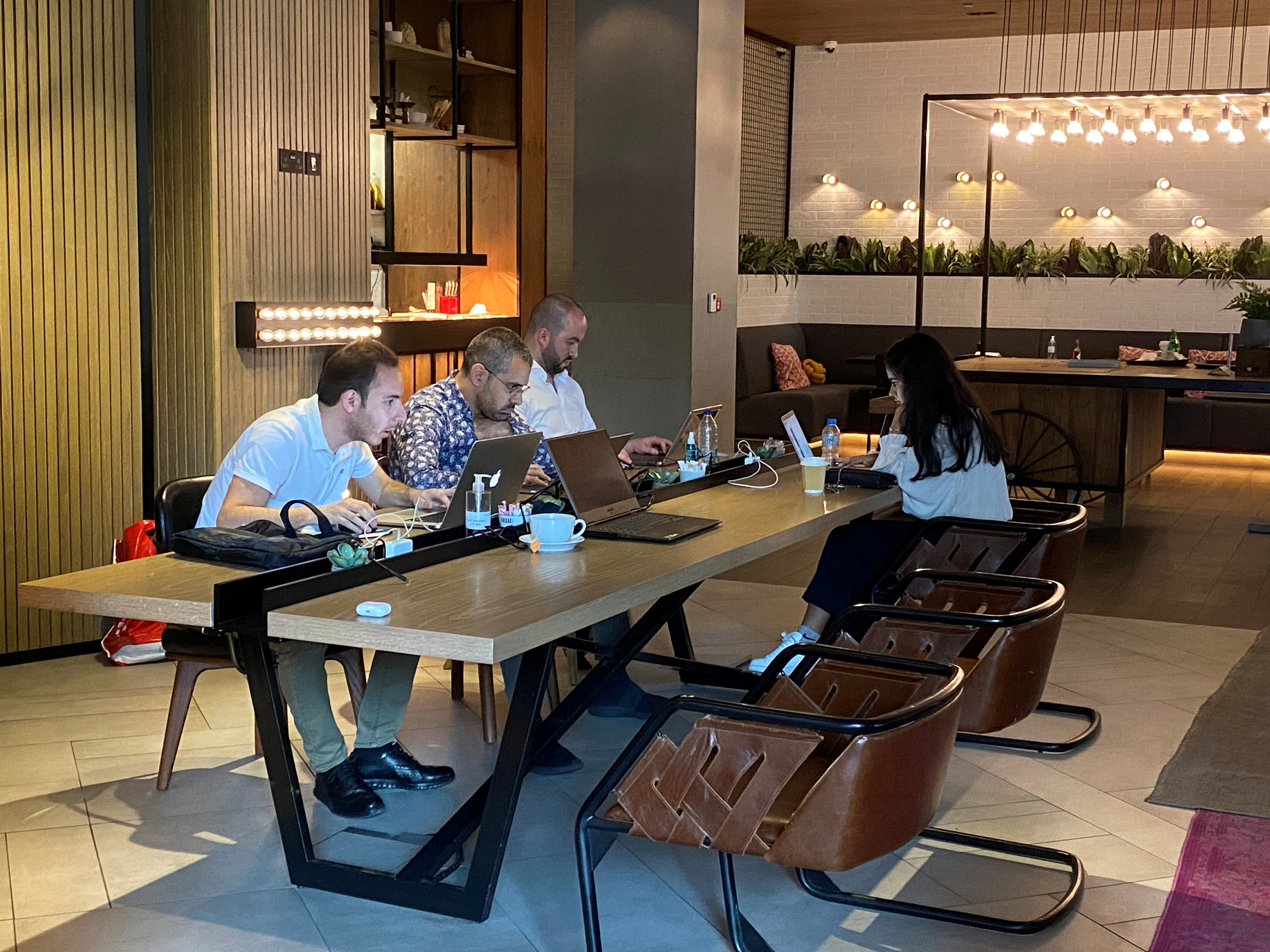 People work as they sit in a cafe at Zabeel House - The Greens, amid the spread of the coronavirus disease (COVID-19) in Dubai, United Arab Emirates February 1, 2021. Picture taken February 1, 2021. REUTERS/Rula Rouhana - RC2UKL9PEICV