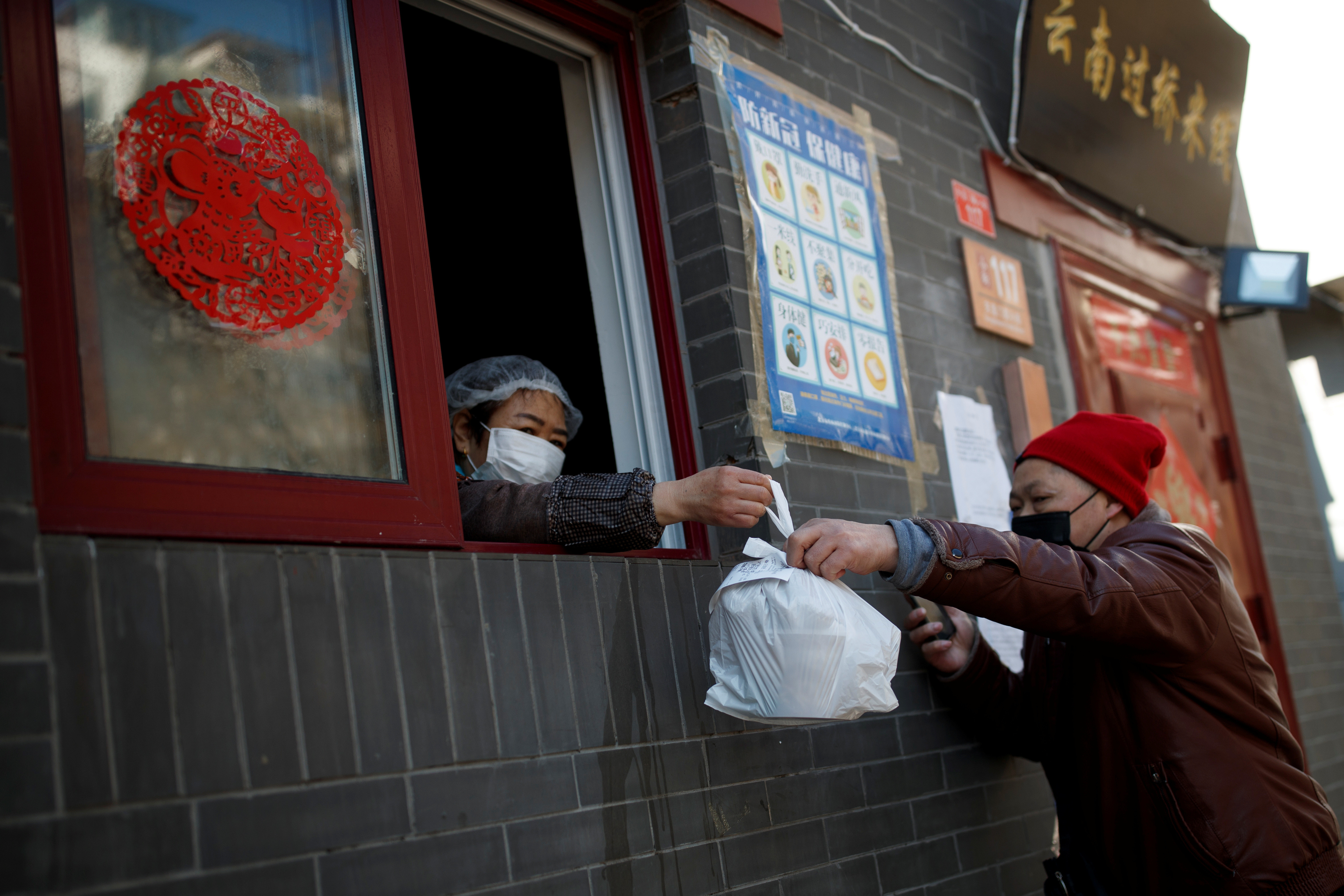 A delivery driver pickes up takeaway food that is handed through the window of a restaurant in Beijing as the country is hit by an outbreak of the novel coronavirus, China, March 3, 2020. REUTERS/Thomas Peter - RC26CF9LM982