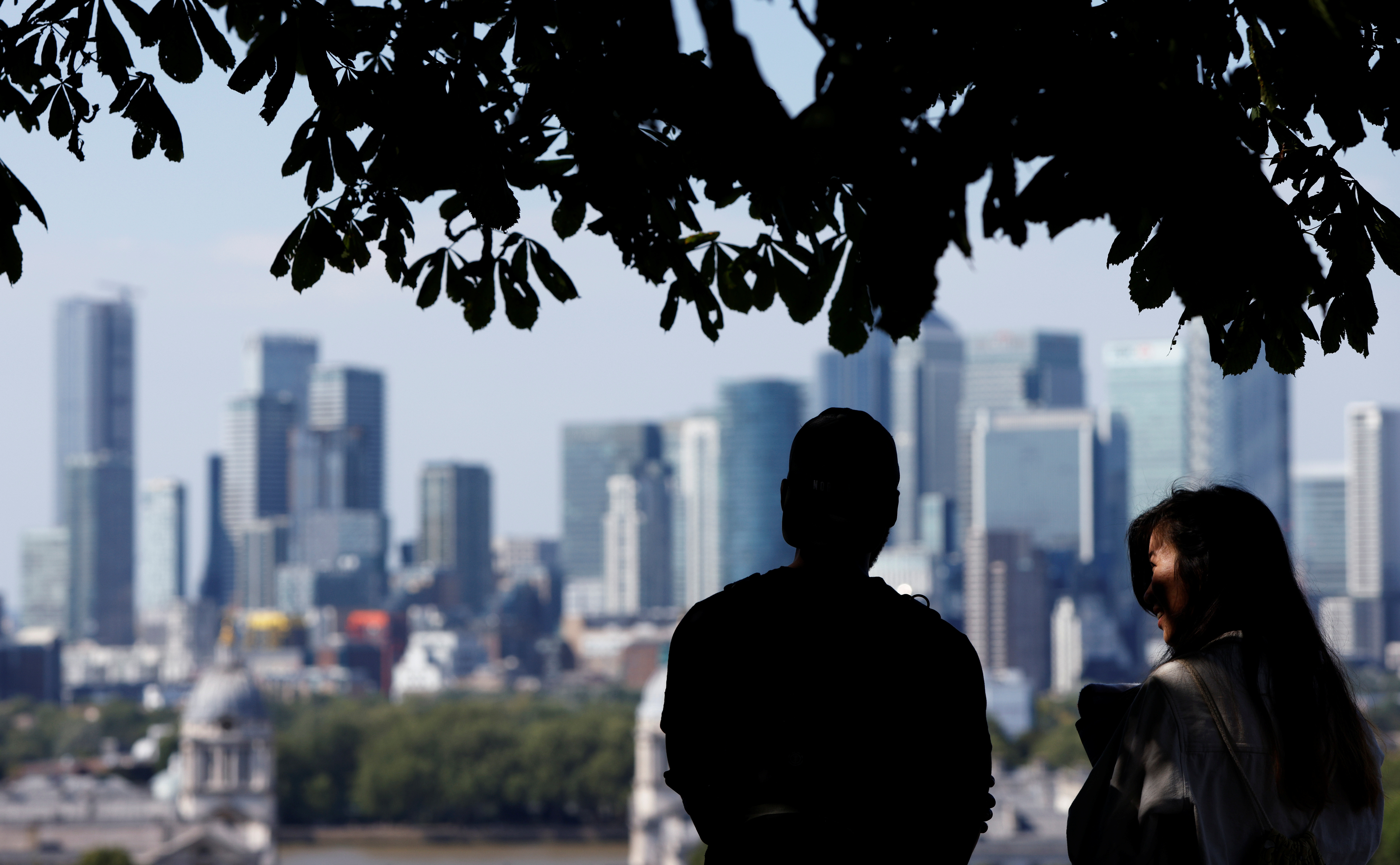 People enjoy the sunny weather in Greenwich Park, with Canary Wharf financial district in the background, in London, Britain, August 7, 2020. REUTERS/John Sibley - RC239I9WL6H9