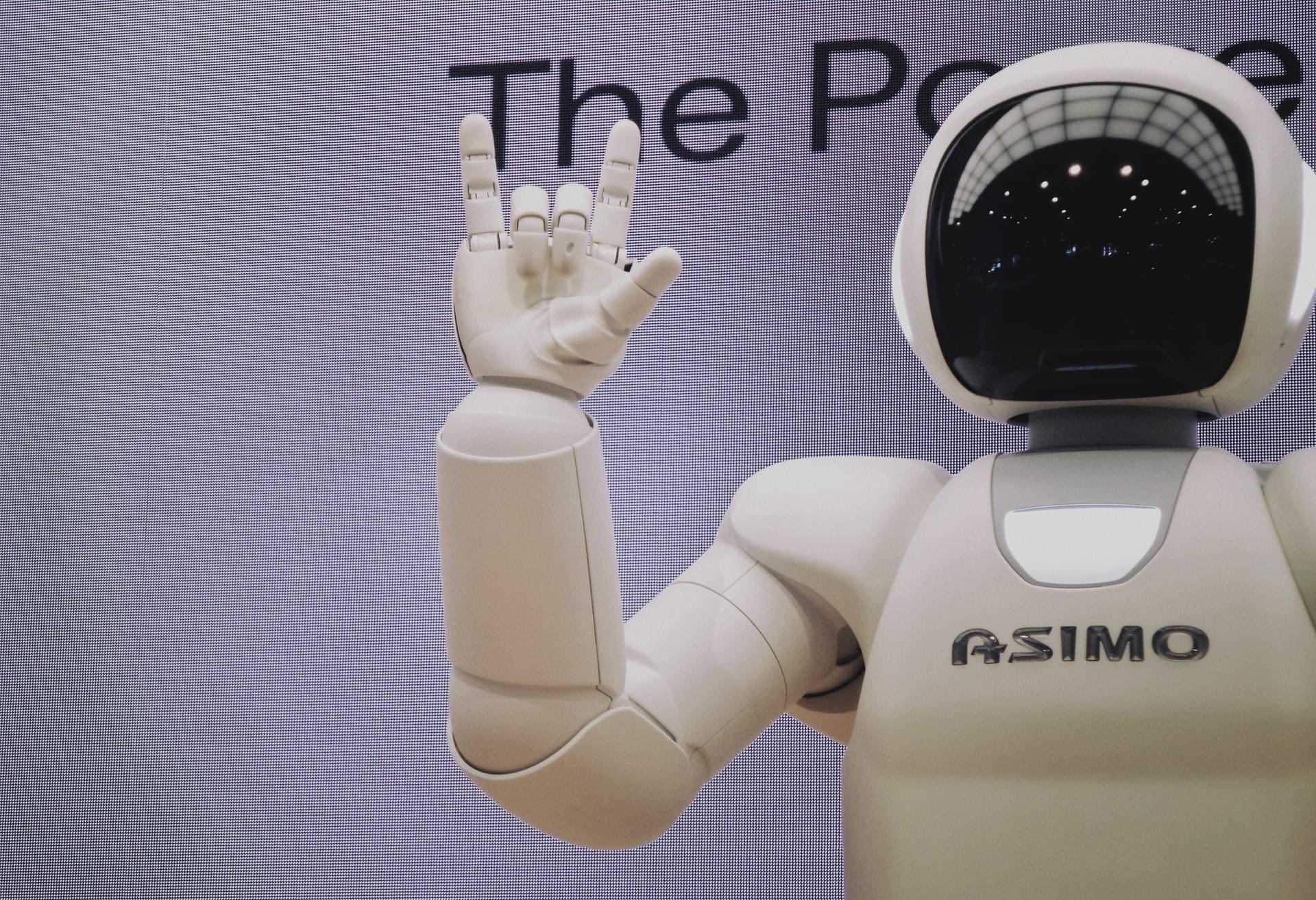 A robot gives a handsign. Unsplash/Possessed Photography