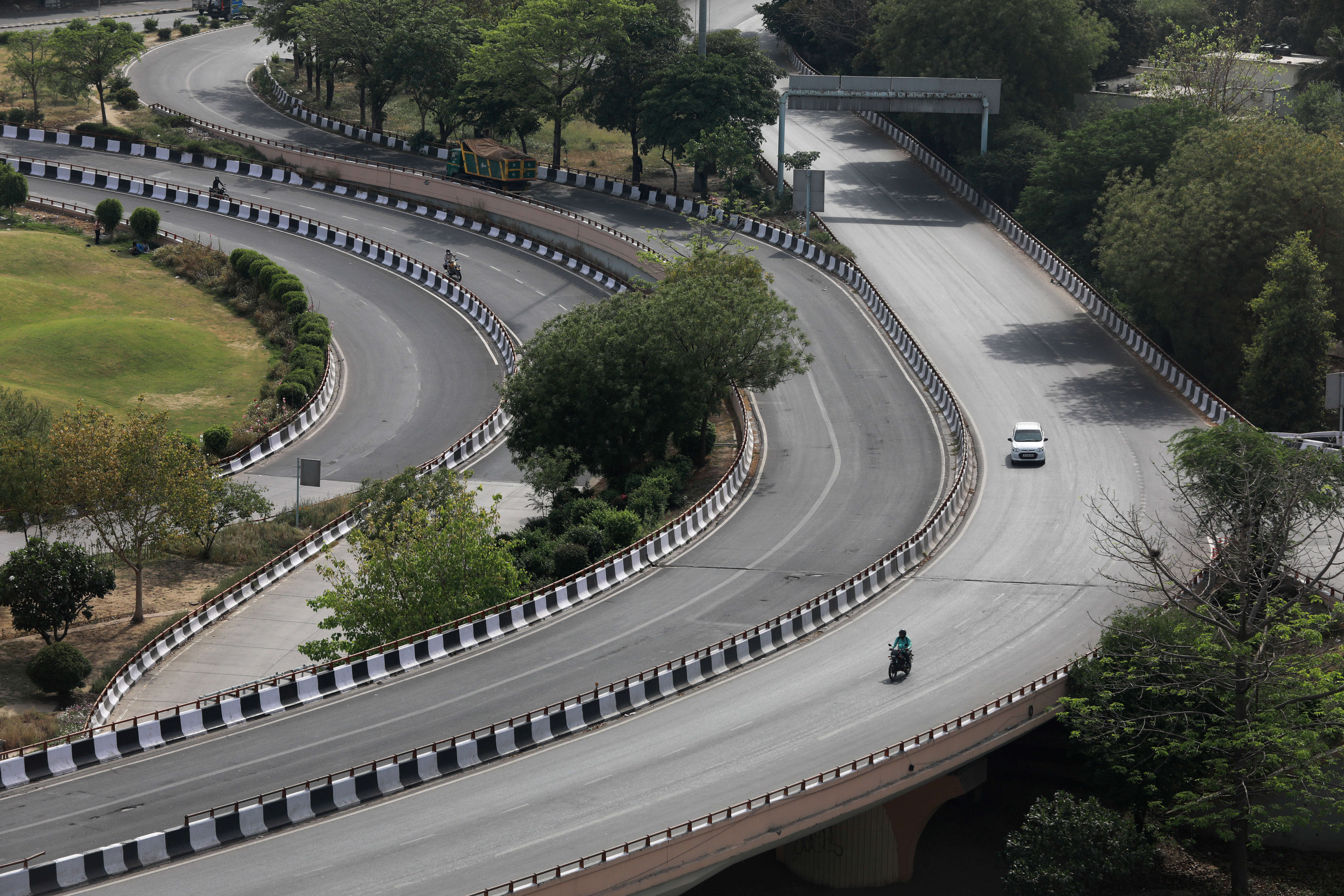Vehicles drive on a nearly empty road after India extended a nationwide lockdown to slow the spreading of coronavirus disease (COVID-19), in New Delhi, April 14, 2020. REUTERS/Anushree Fadnavis - RC2D4G9TD3CY